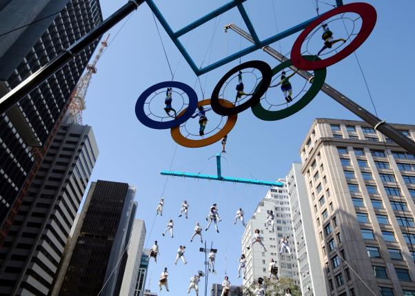 Acrobats perform on the Olympics rings at Paulista Avenue in Sao Paulo's financial center