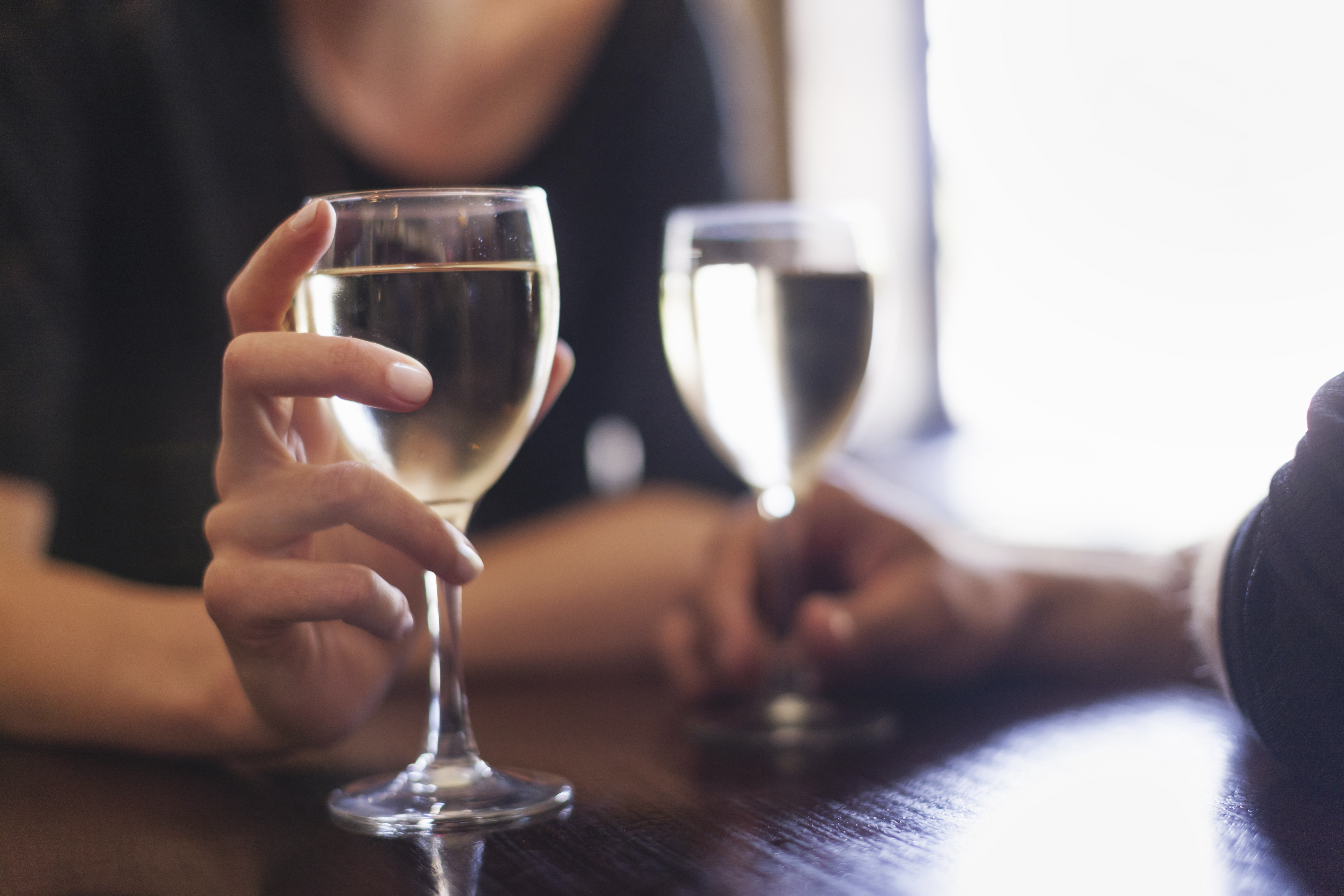 Two people, a couple sitting in a bar having a glass of chilled white wine.