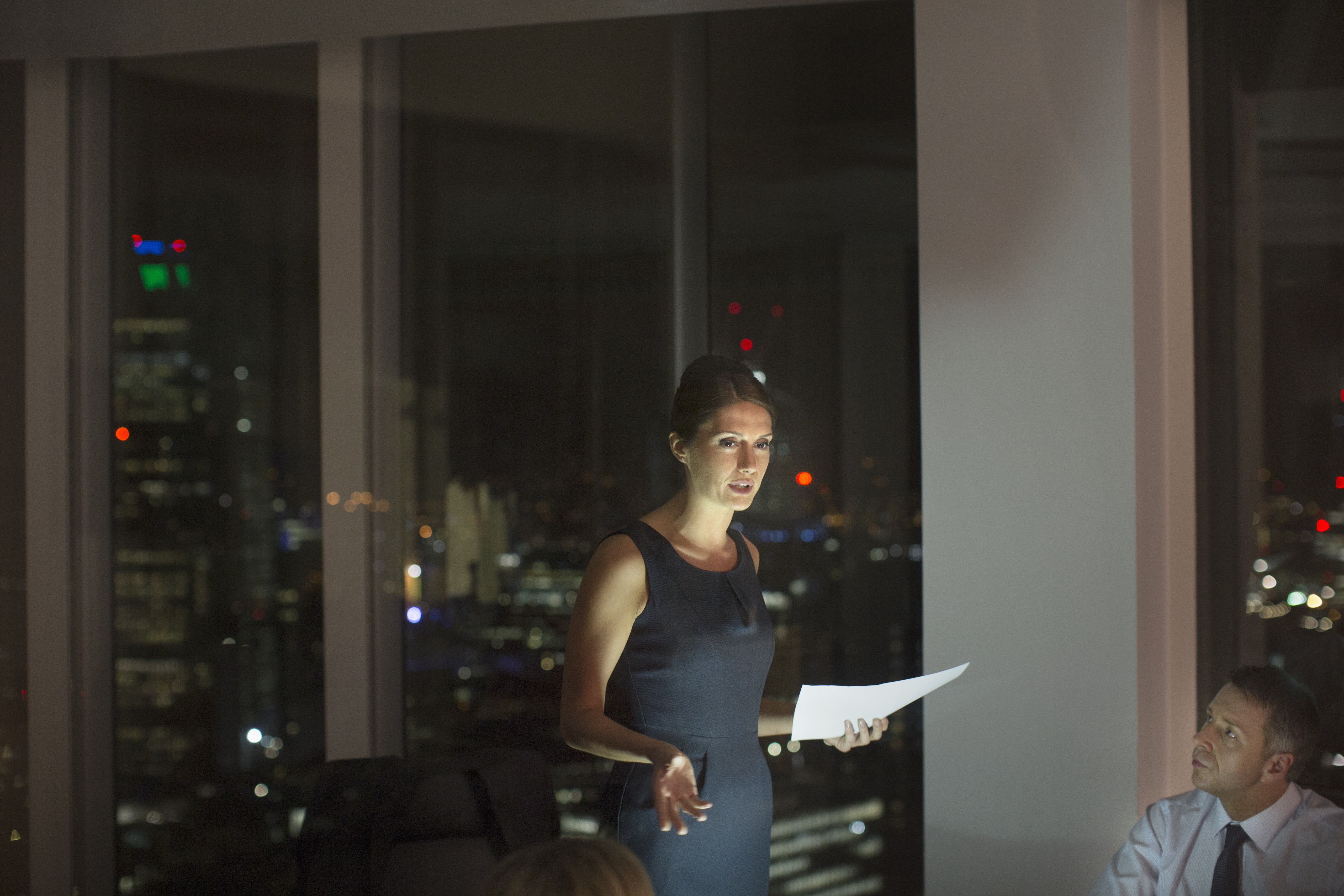 Businesswoman leading meeting in conference room at night