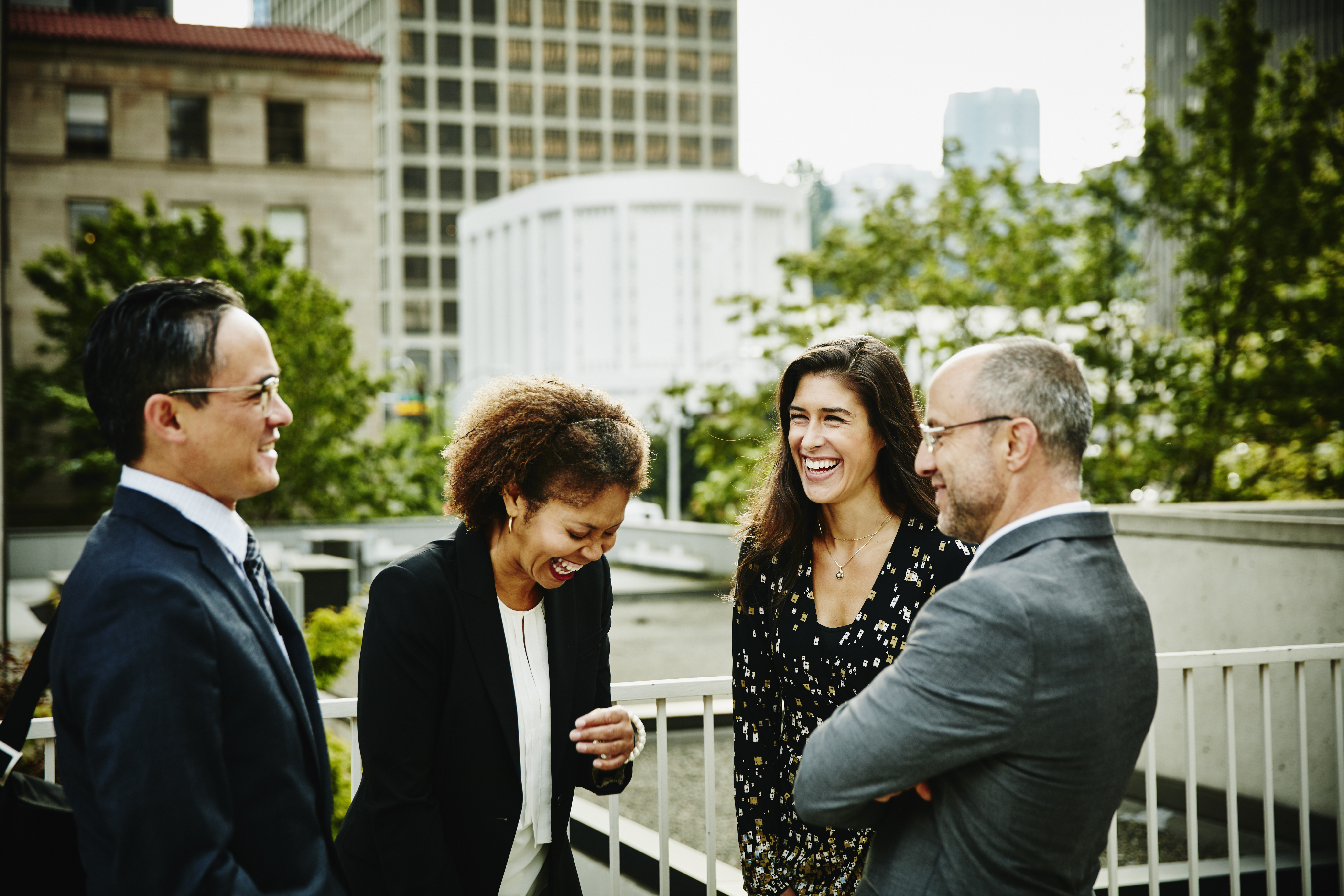 Laughing business colleagues in discussion outside
