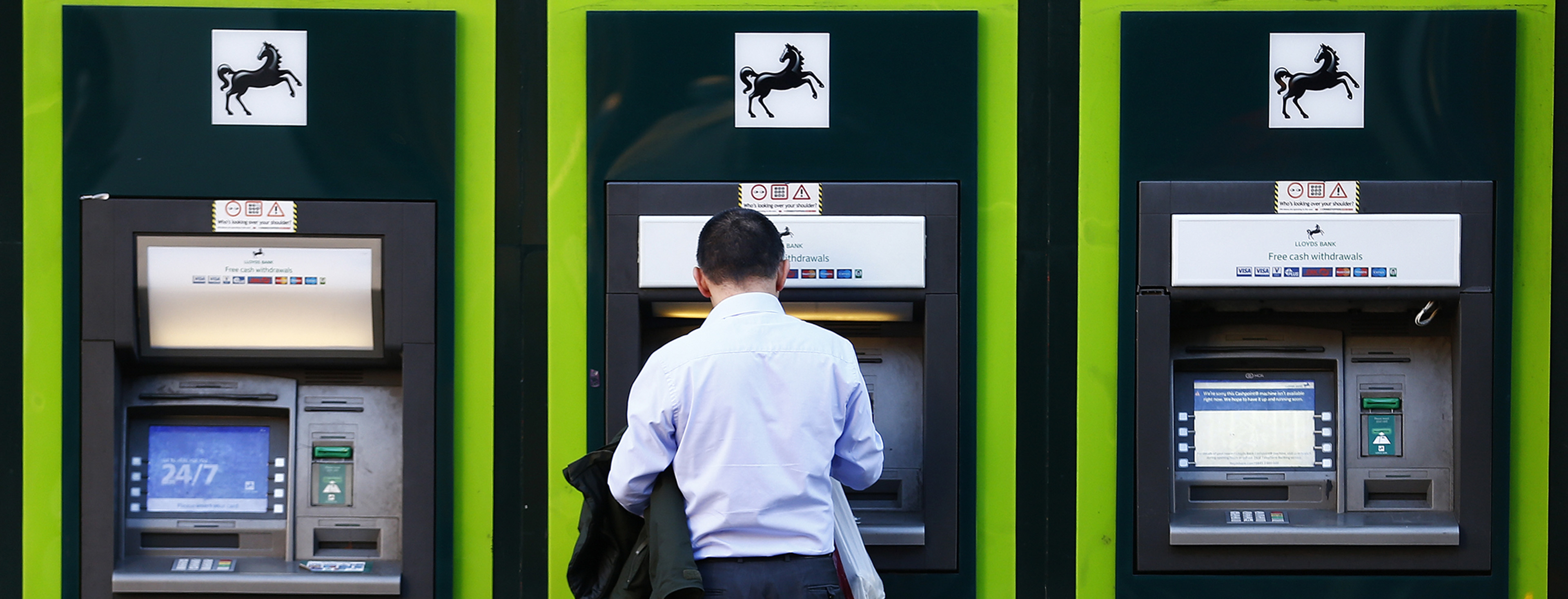 A man uses an ATM  outside a branch of Lloyds Bank in central London