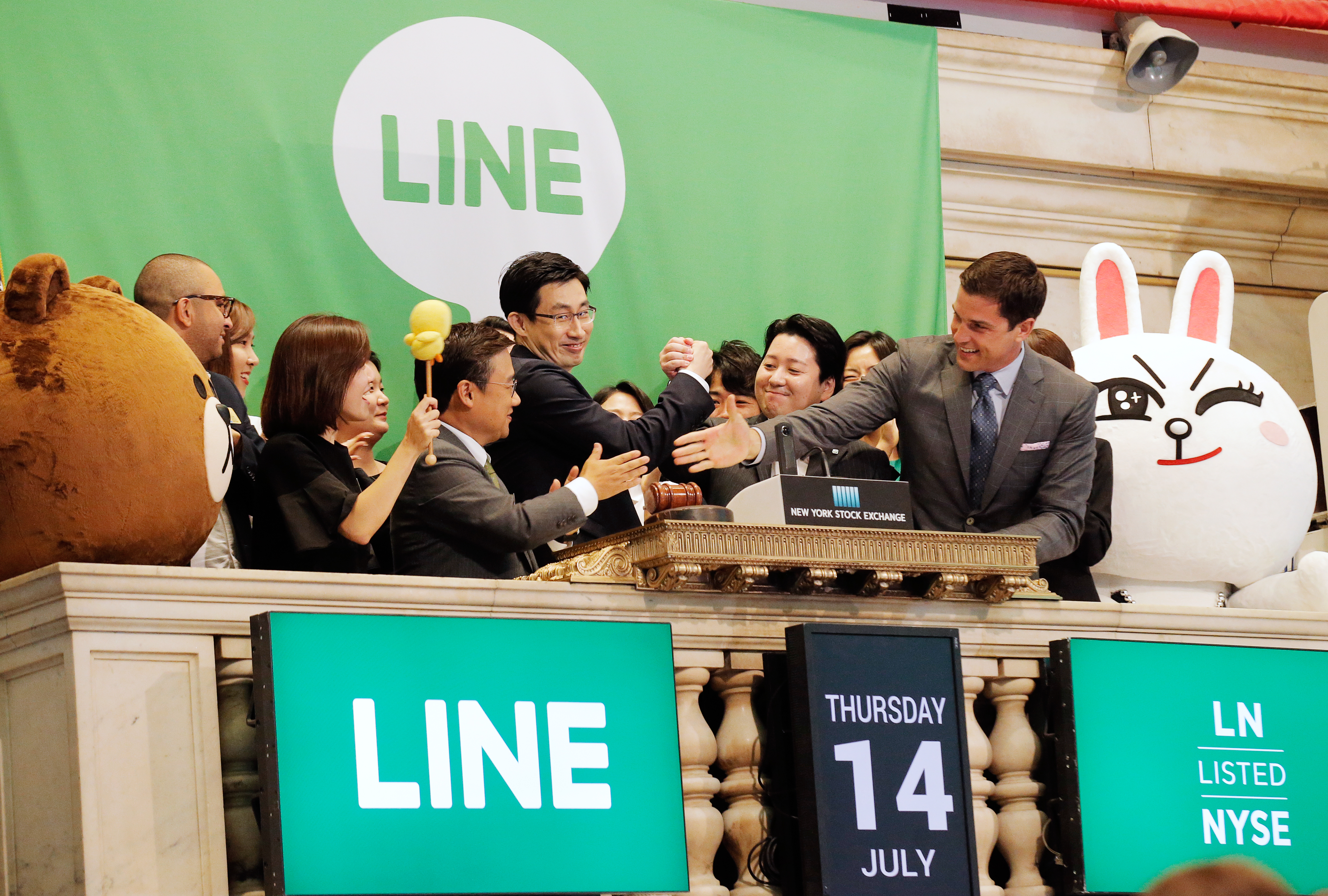 NYSE president Tom Farley congratulates Japan's Line Corp. CFO In-Joon Hwang and Chief Global Officer Joongho Shin and Chief Strategy and Marketing Officer Jun Masuda during the company's IPO on the floor of the New York Stock Exchange