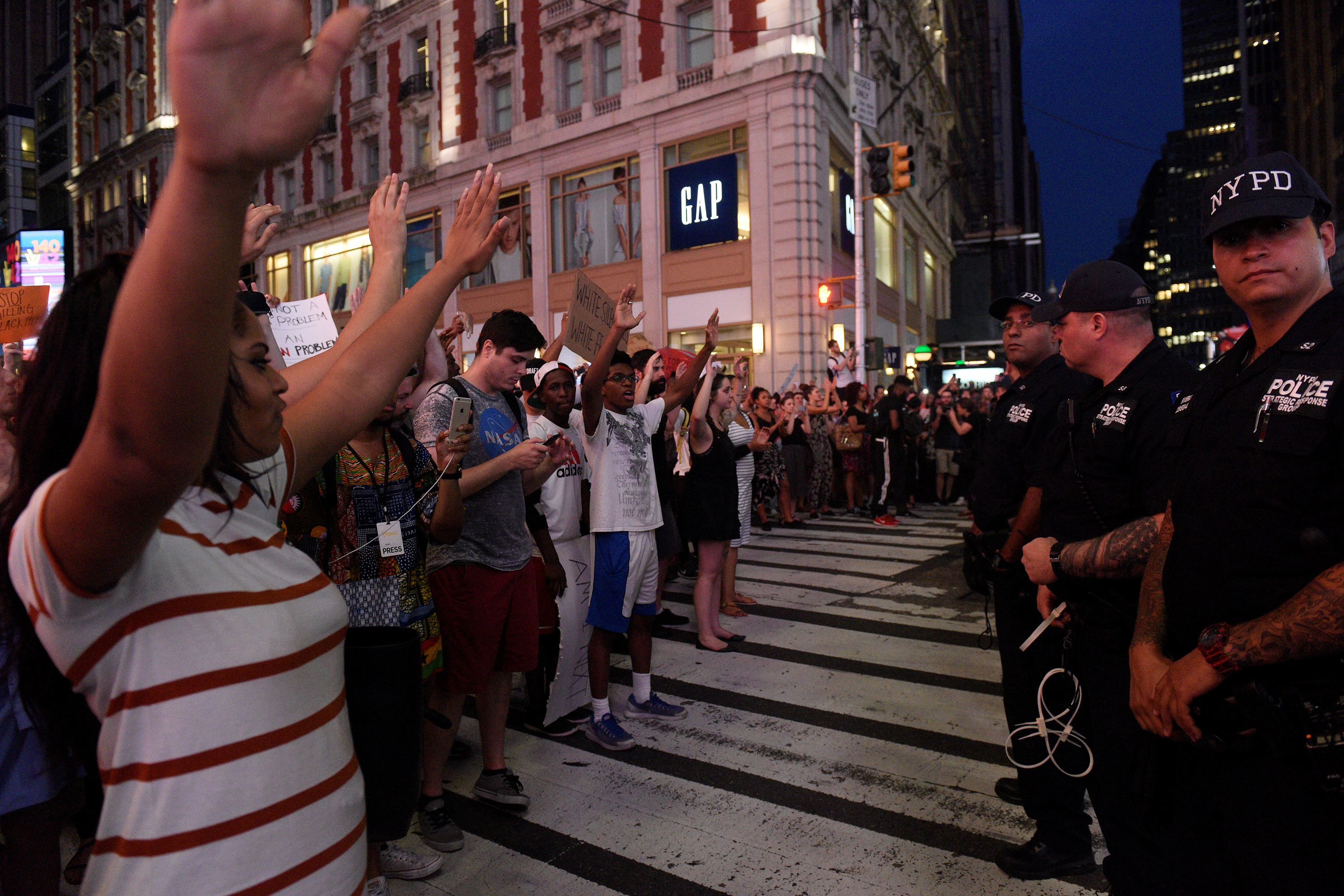 "People hold their hands in the air as they yell ""hands up, don't shoot!"" during a protest for the killing of Alton Sterling and Philando Castile in the Manhattan borough of New York"