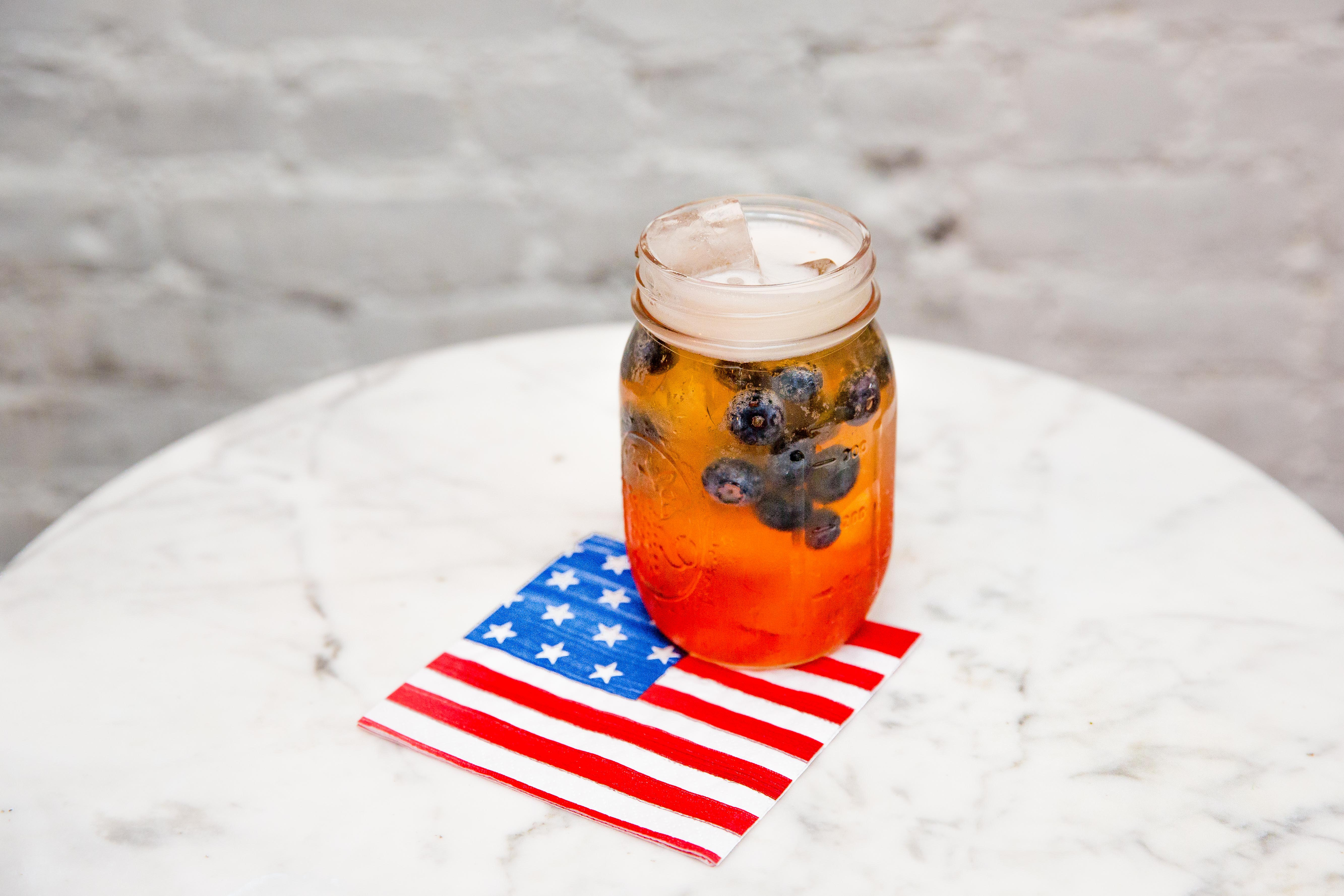 This cocktail, called Stars + Stripes, is made with Domaine de Canton Ginger Liqueur, Aperol and Schofferhofer grapefruit beer. It is garnished with blueberries or a slice of grapefruit.