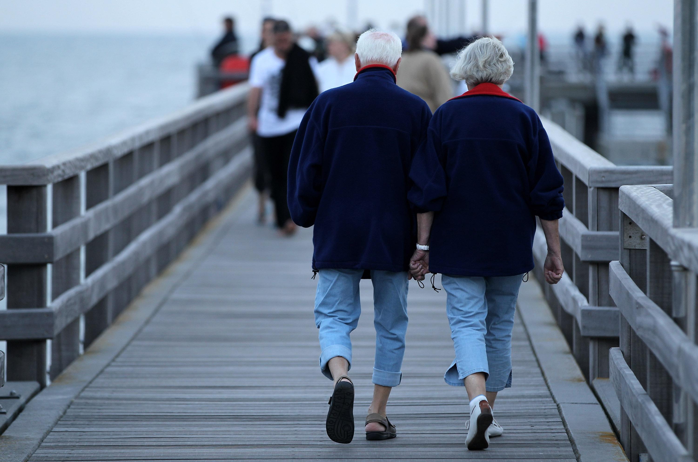 An elderly couple walks on a pier near the Baltic Sea in Germany.