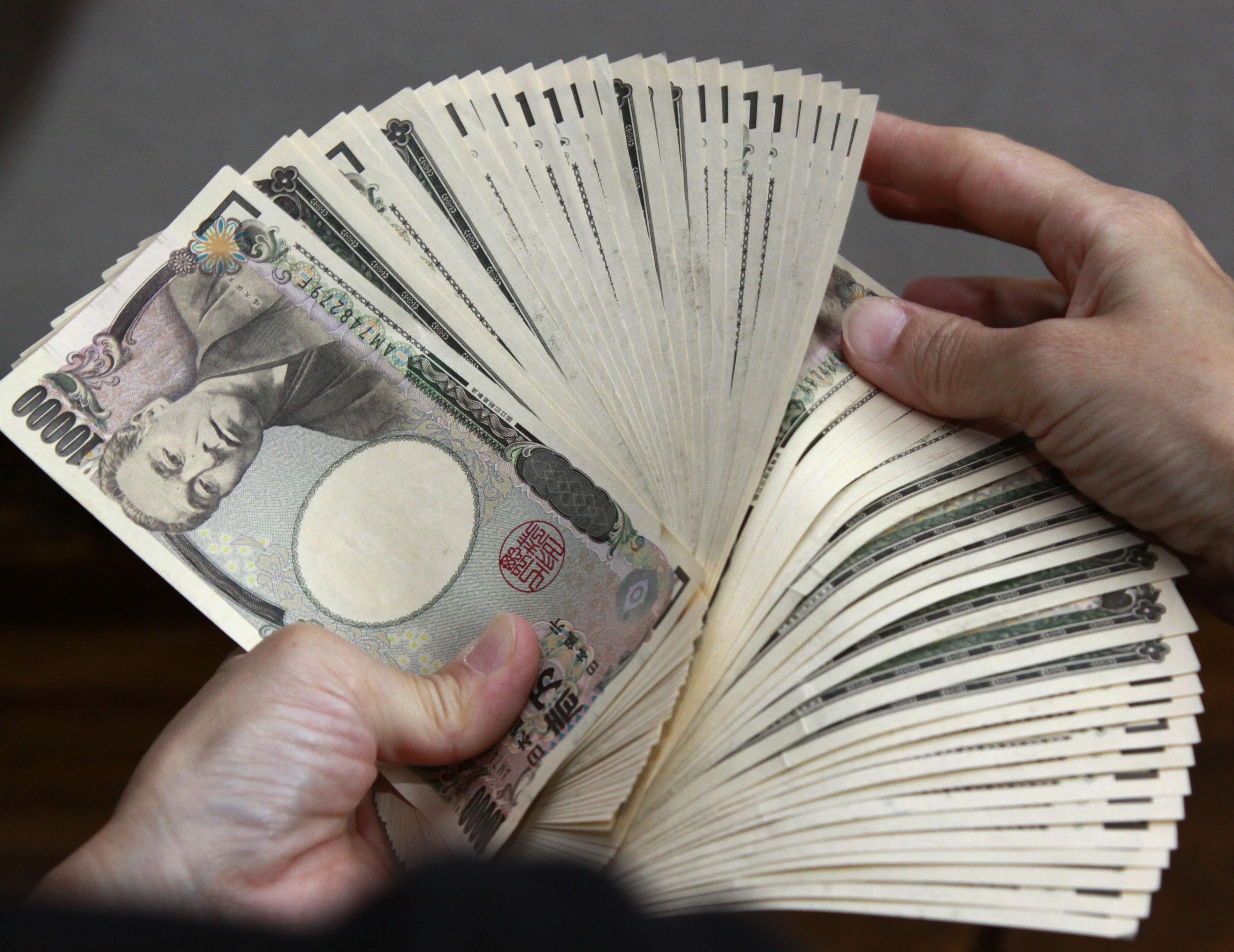 A bank teller counts 10,000 yen (118 USD