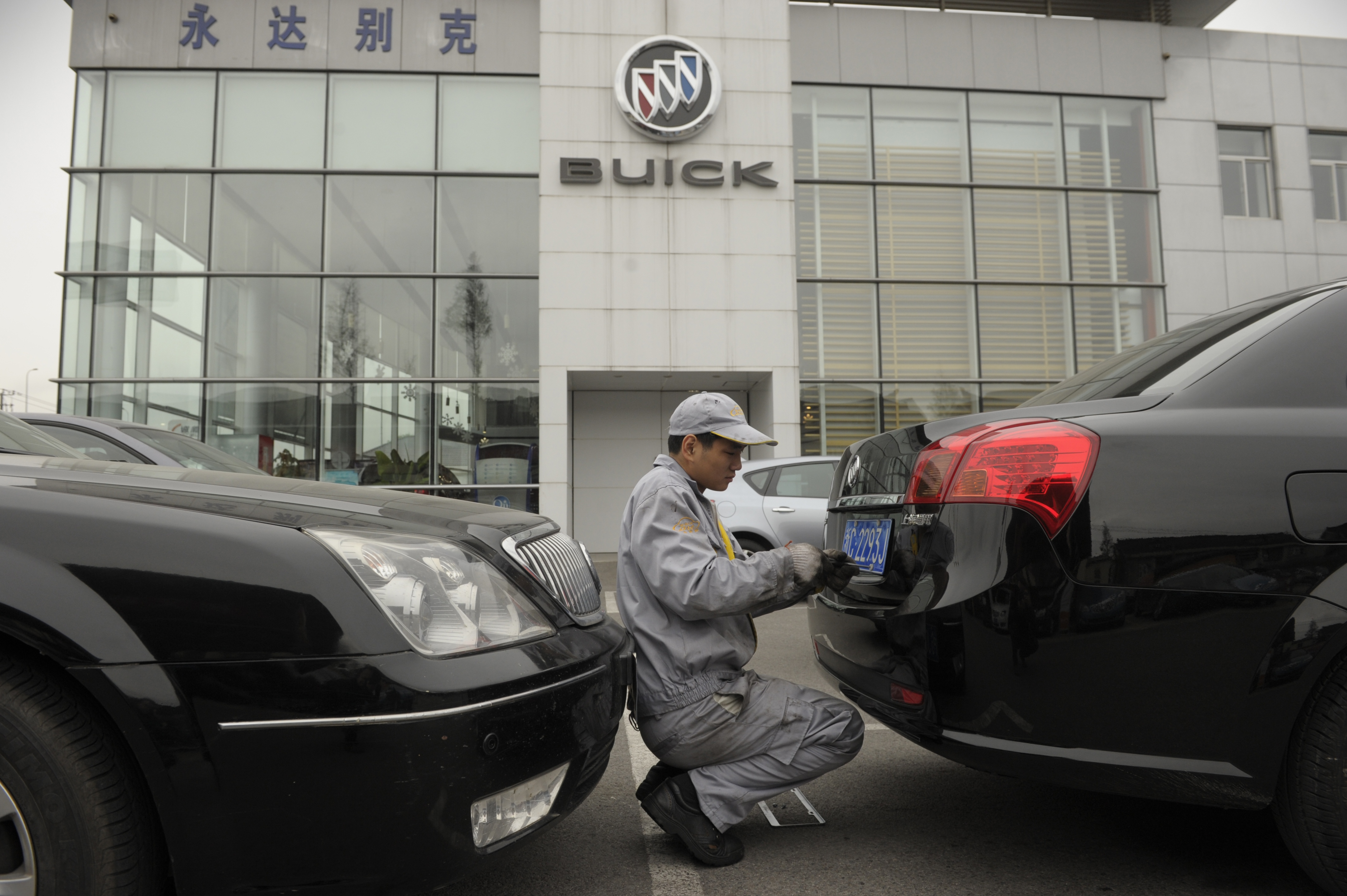 A mechanic works on a Buick at a General