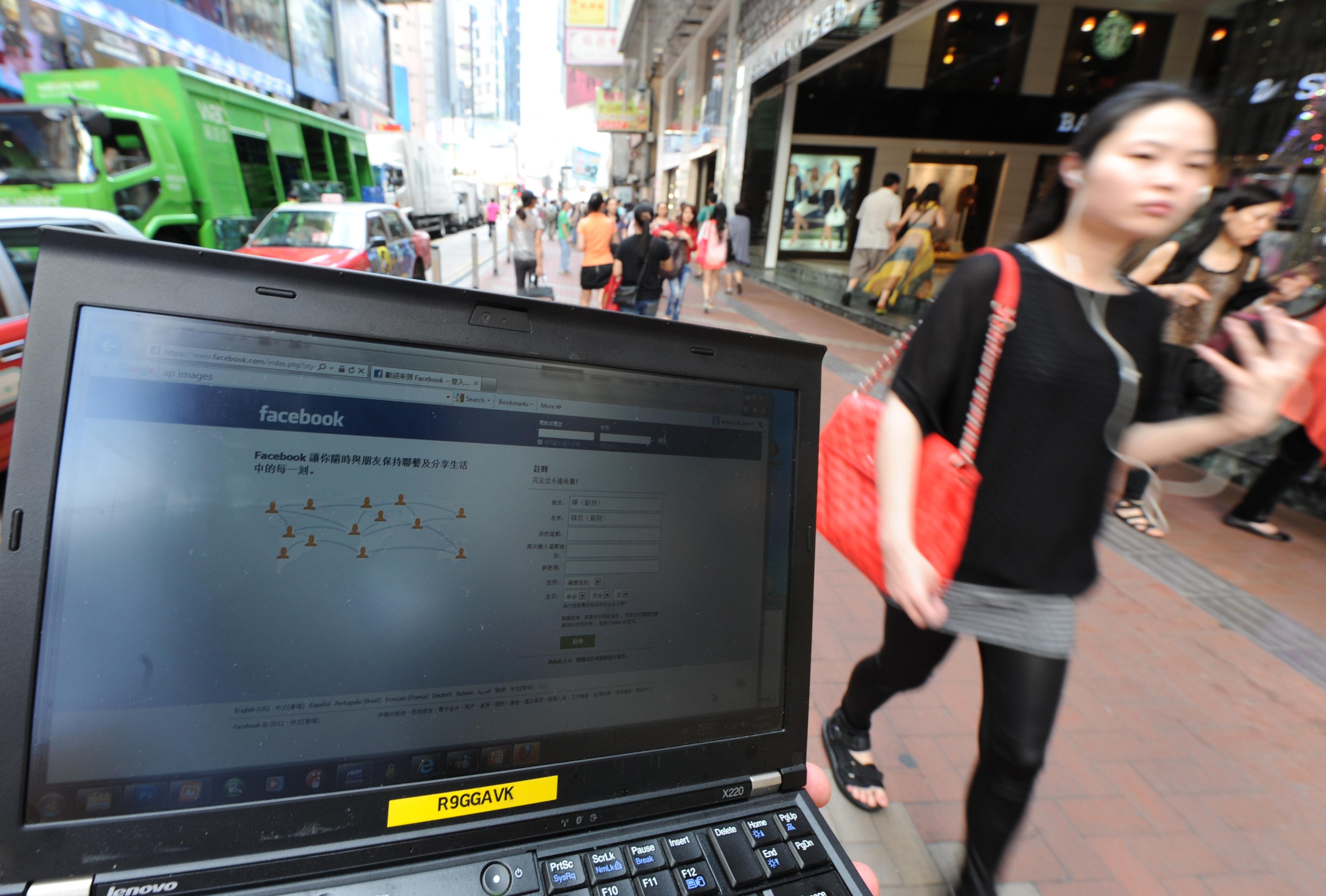 A pedestrian walks past a computer showi