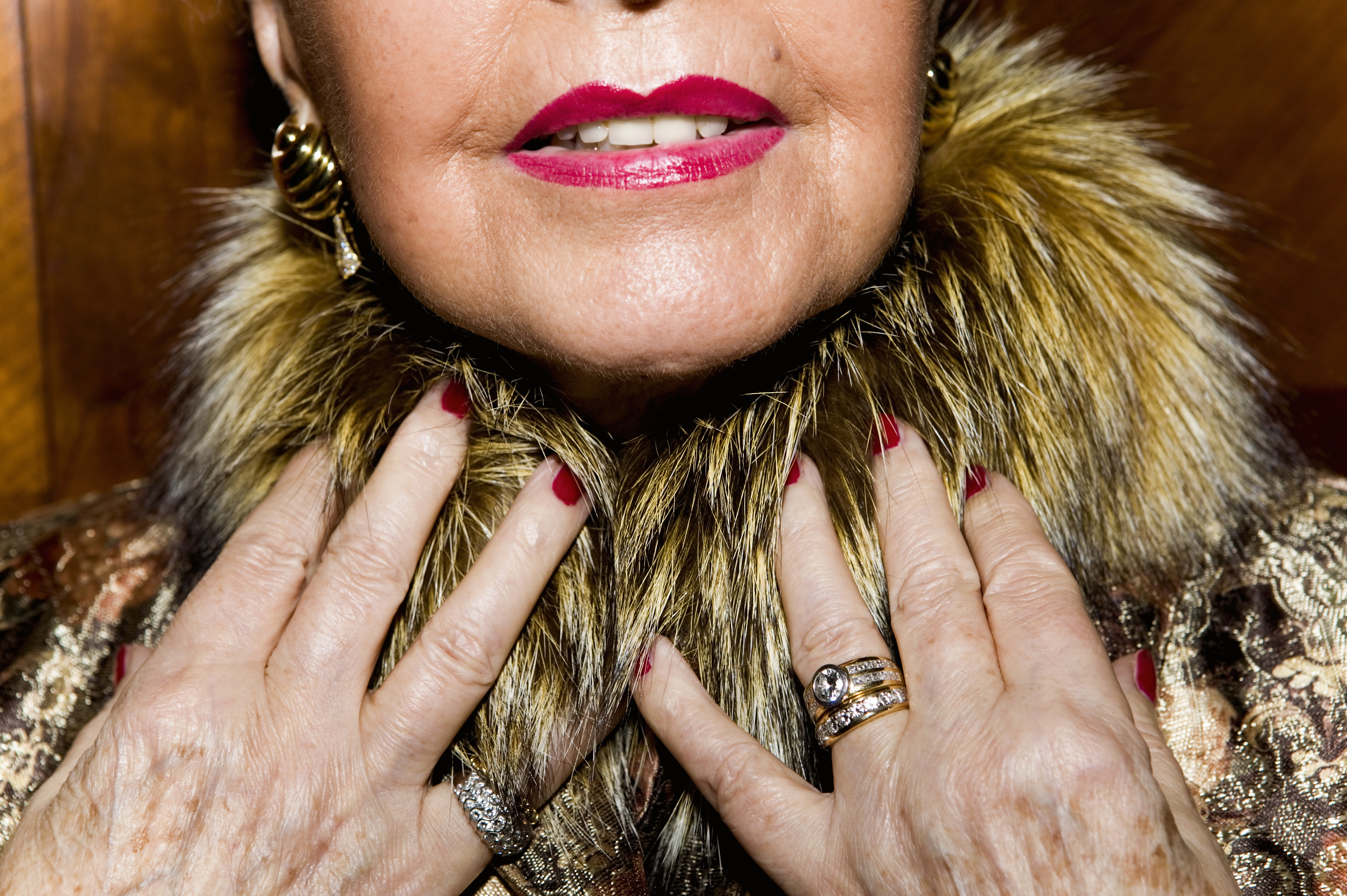 Senior woman wearing fur collared coat and rings, close-up