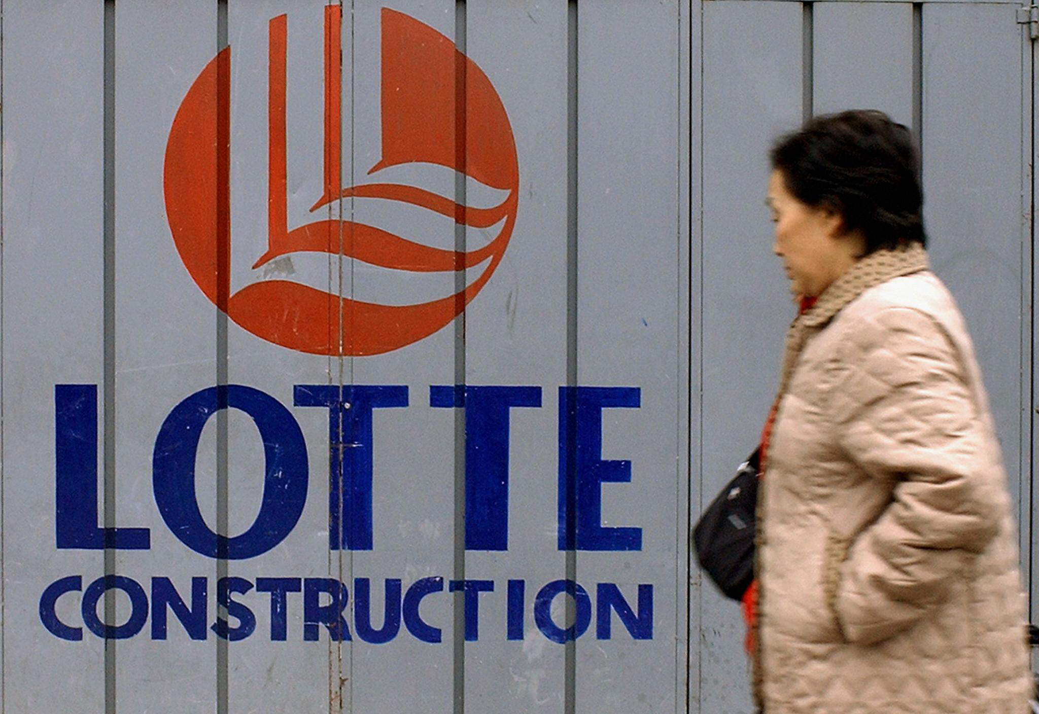 A woman walks past a logo of Lotte Group