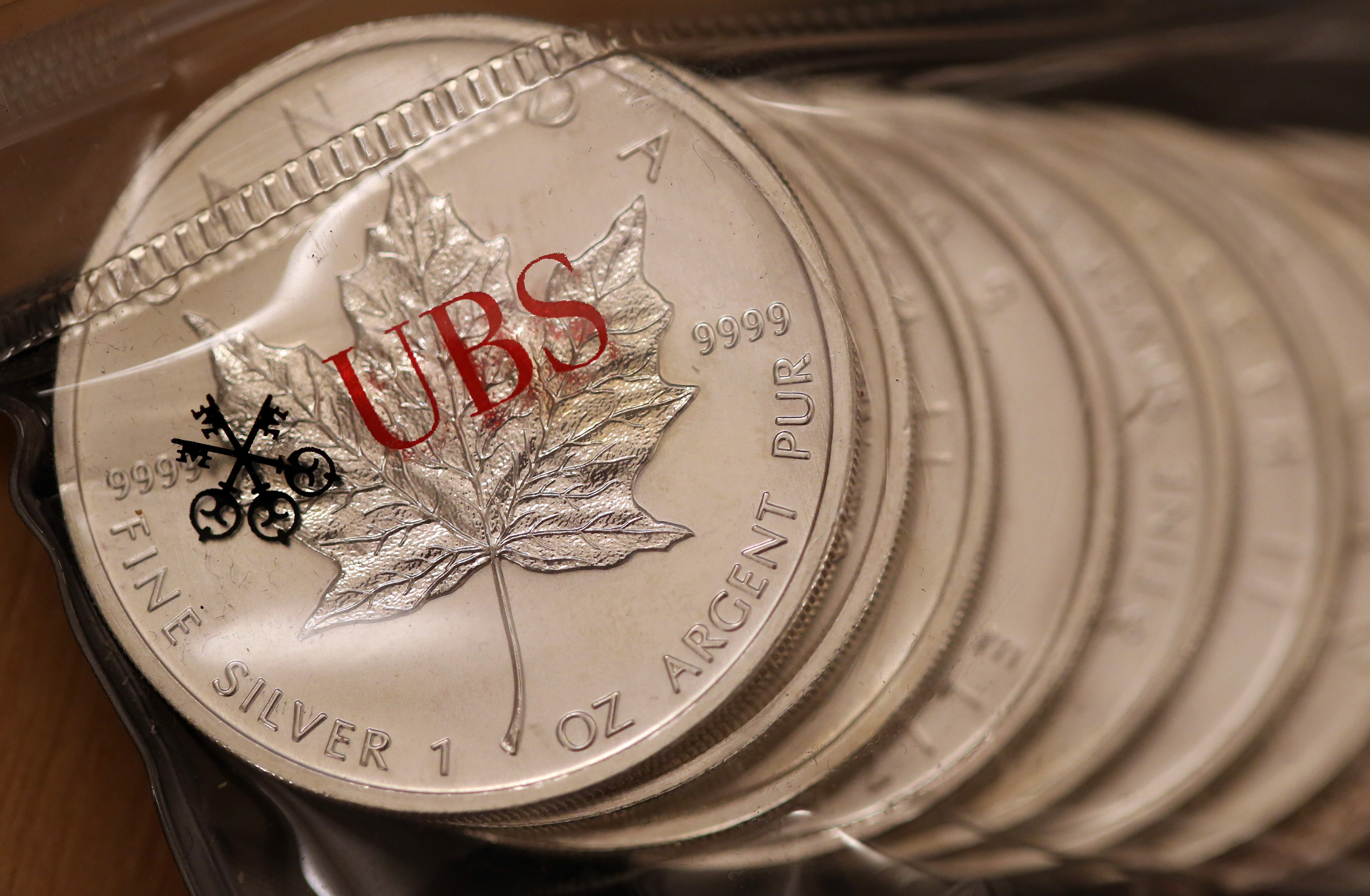 One ounce silver coins sit stored inside a UBS branded plastic bag in London.