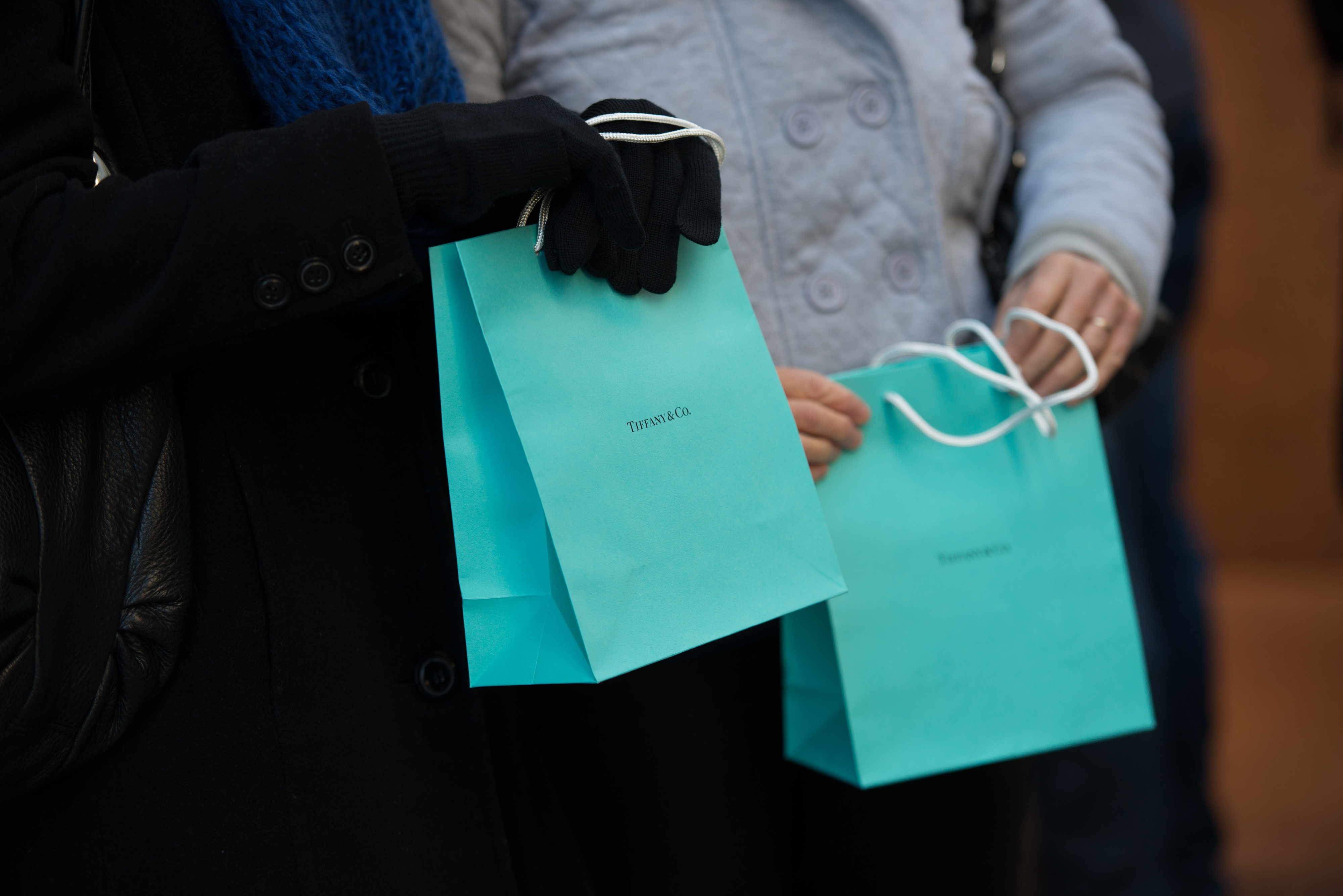 Customers carry Tiffany & Co. shopping bags outside the company's flagship store in New York.