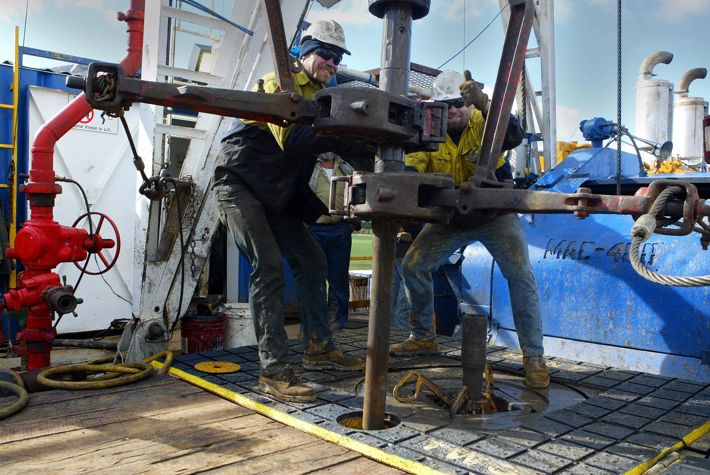 Workers change out a pipe on The Bellarine 1 drilling rig west of Geelong. The