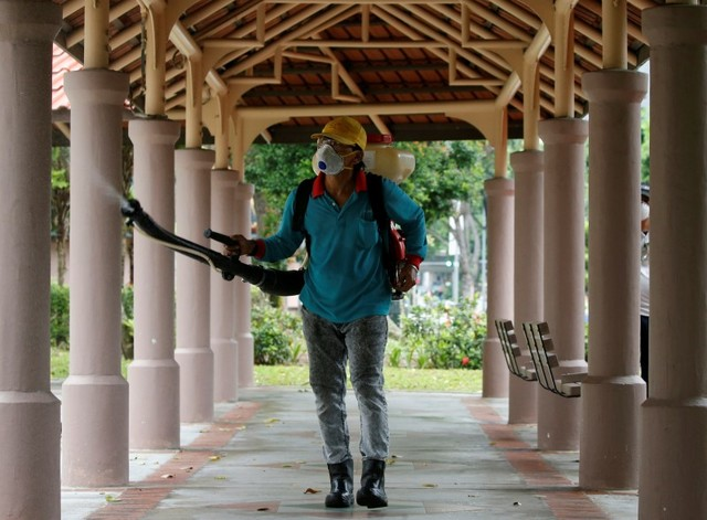 A worker mists the common area of a public housing estate with insecticide in Singapore