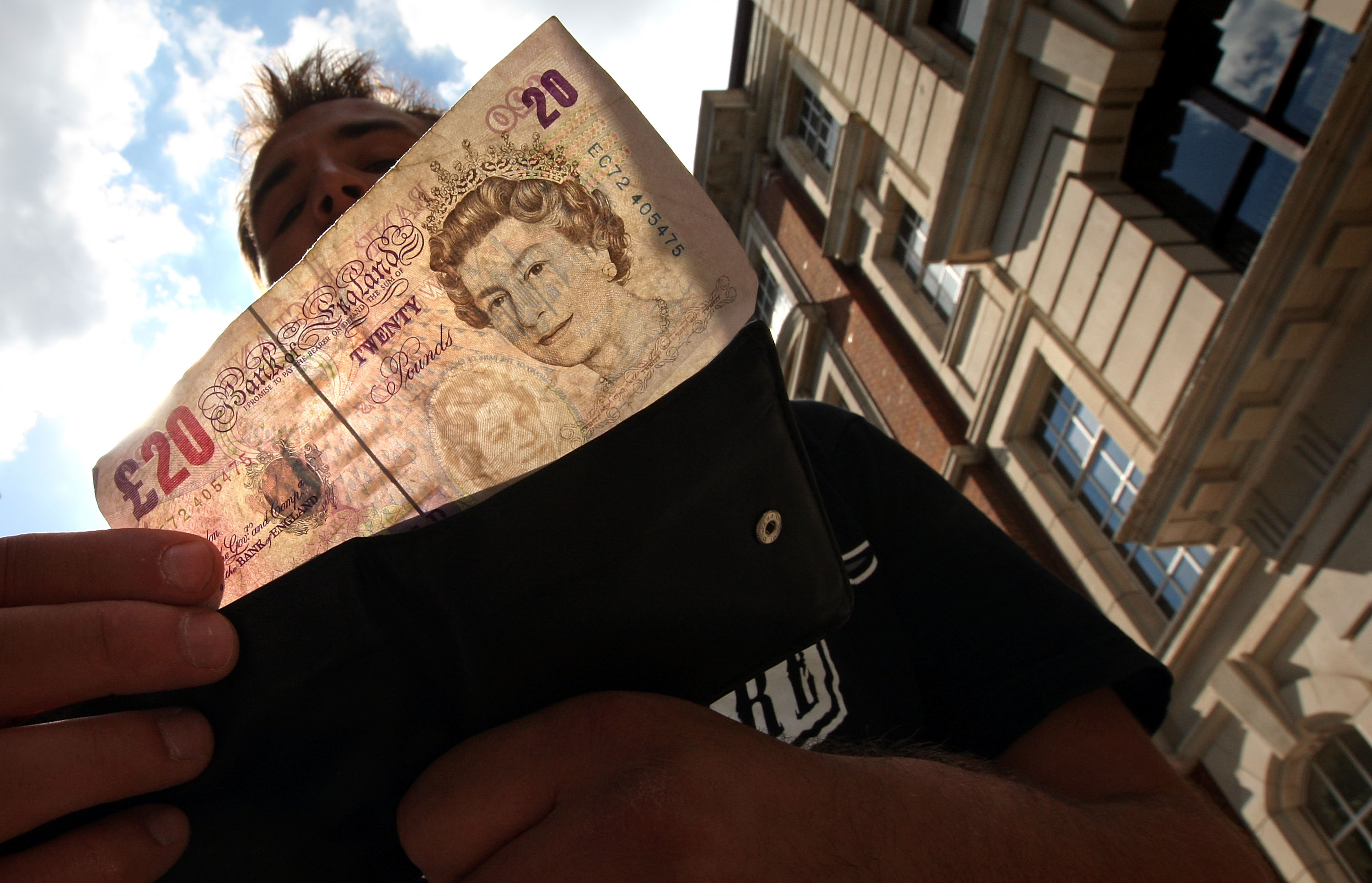 A man takes a 20 pound note from his wallet outside a bank in London.