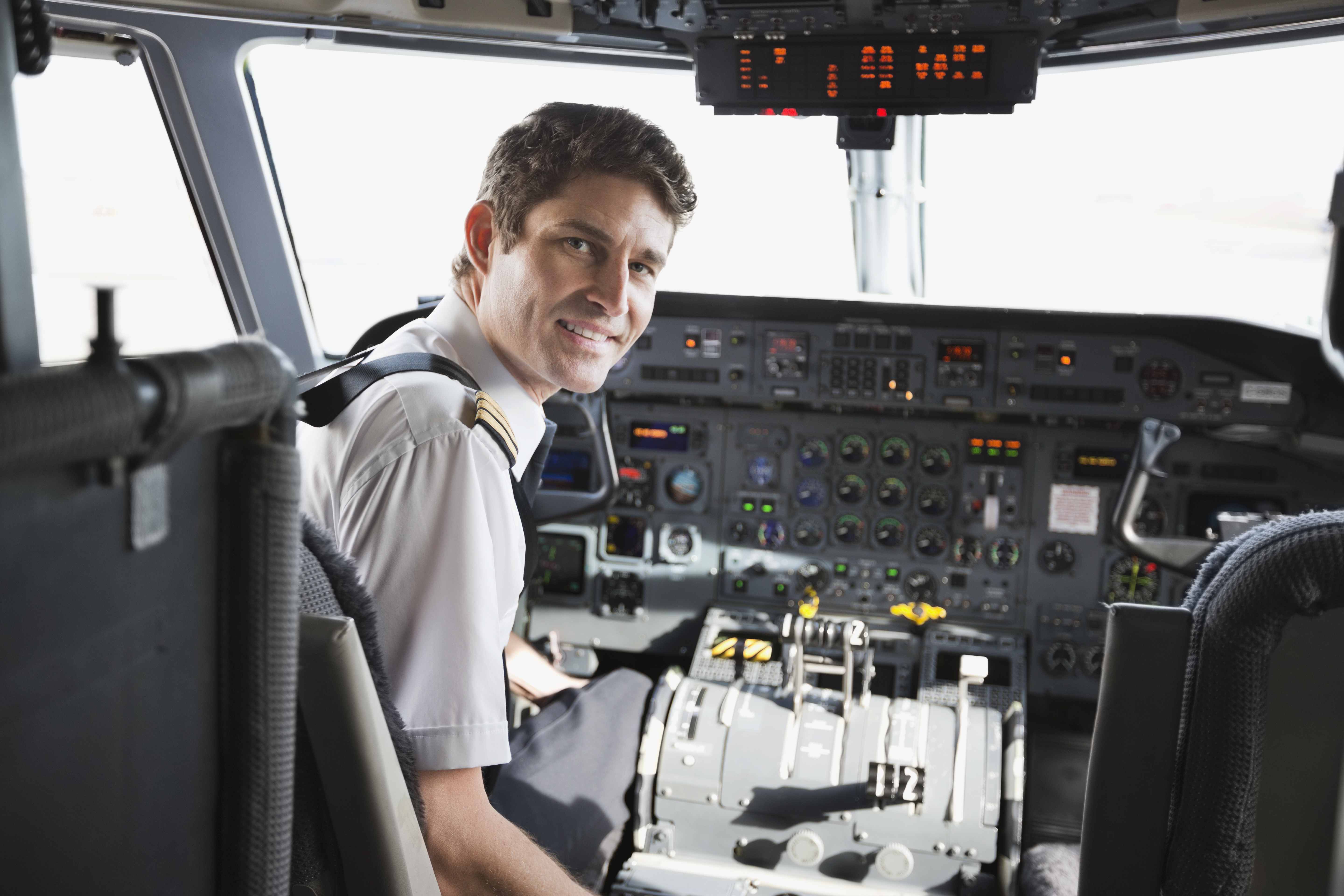 Portrait of male pilot sitting in airplane cockpit