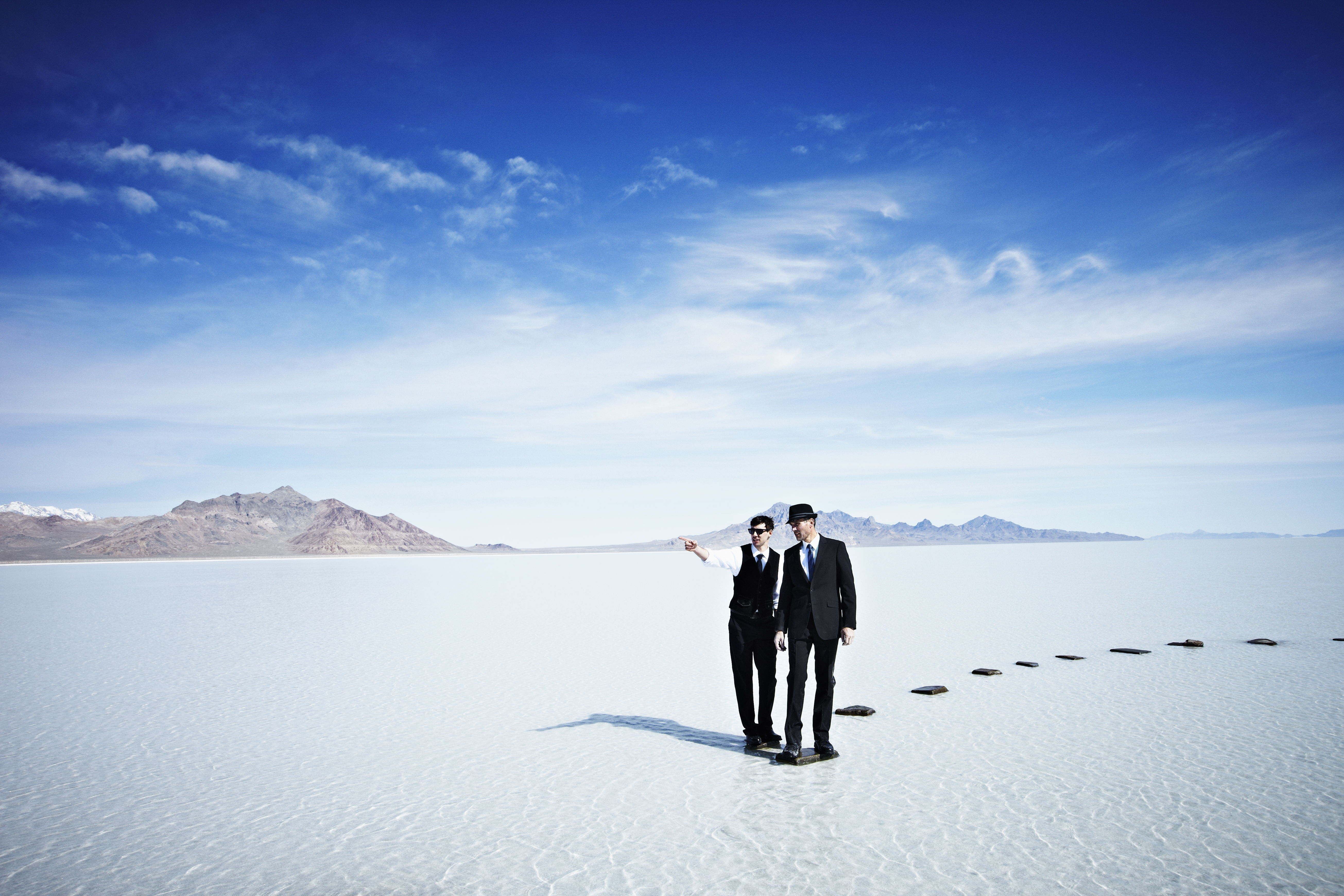 Businessmen standing at end of pathway in lake