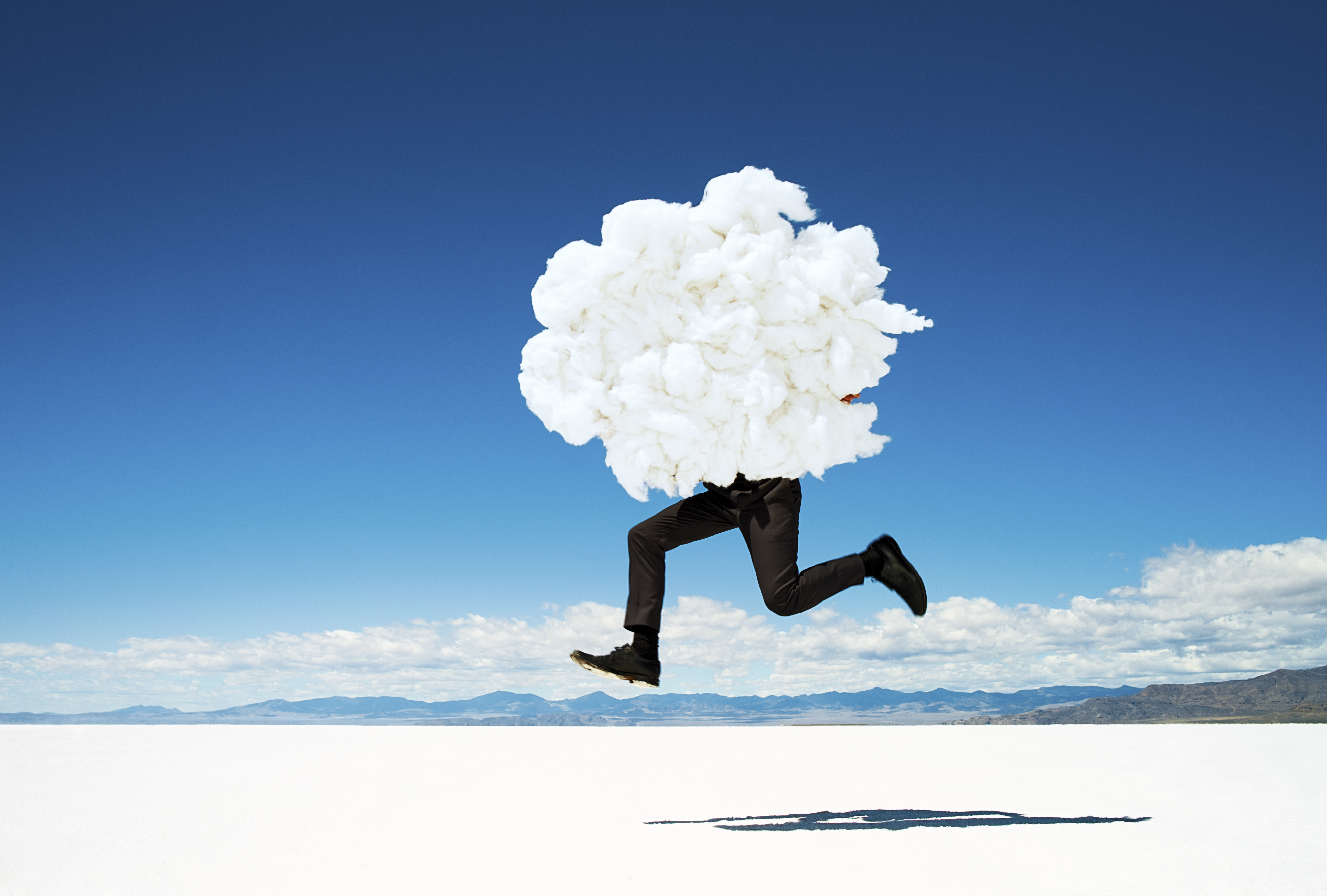 Man leaping on salt flats holding giant cloud.