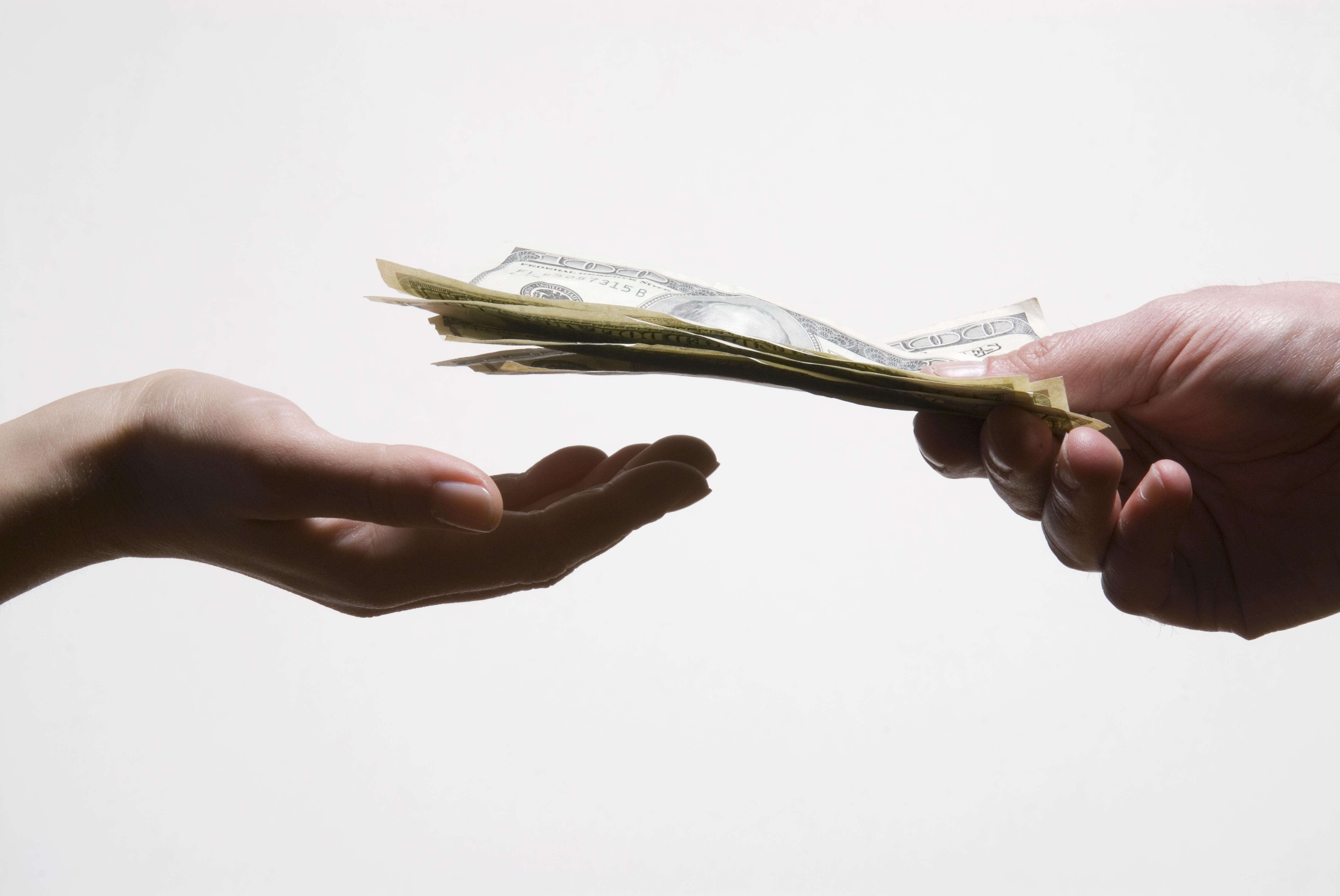 Man handing woman US dollar banknotes, close-up