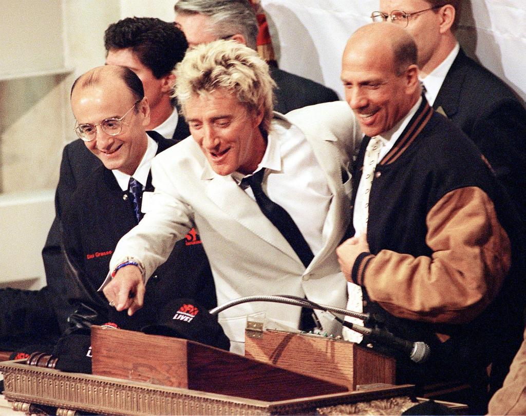Rock musician Rod Stewart (C) points to someone on