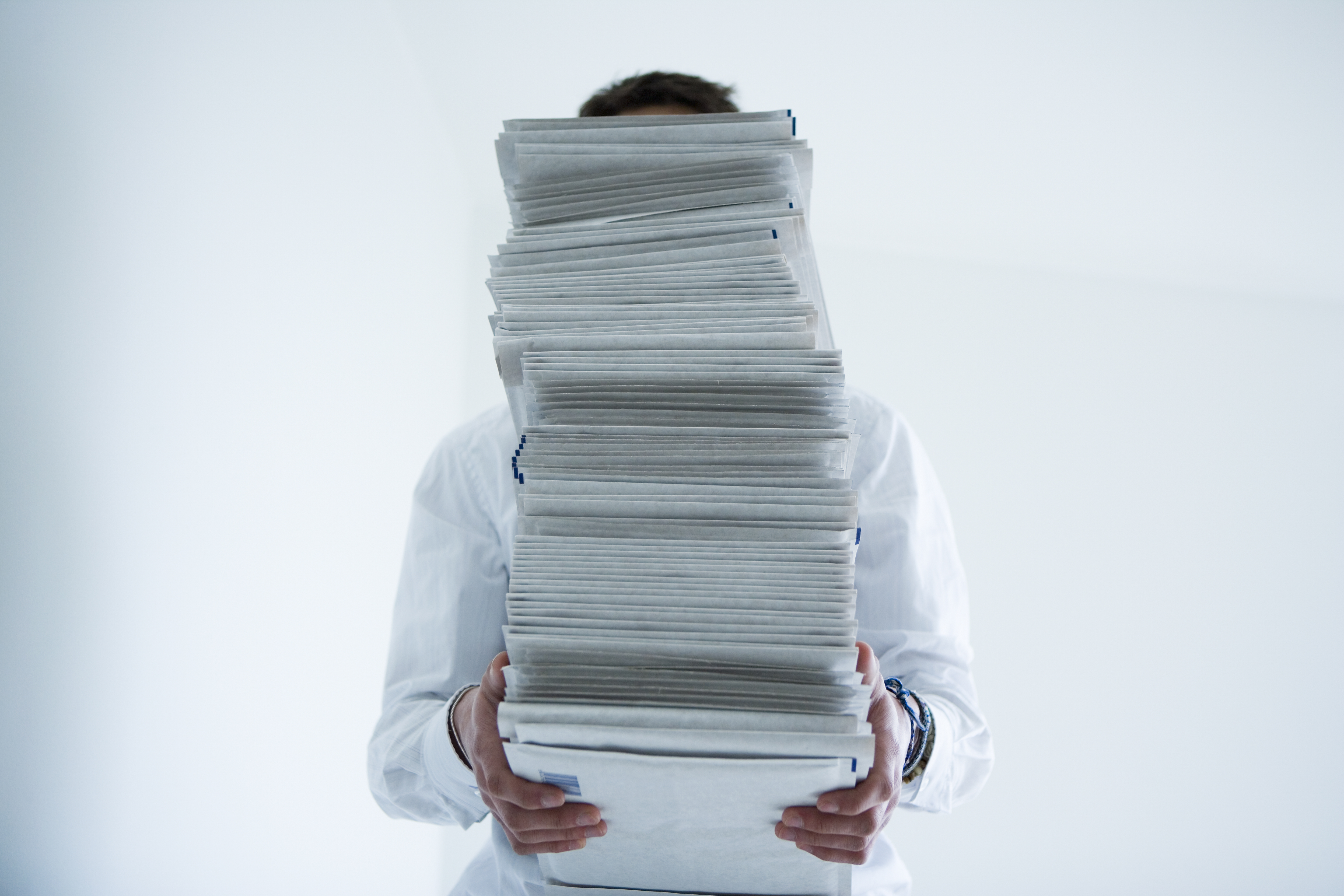 Man holding stack of paper in front of face
