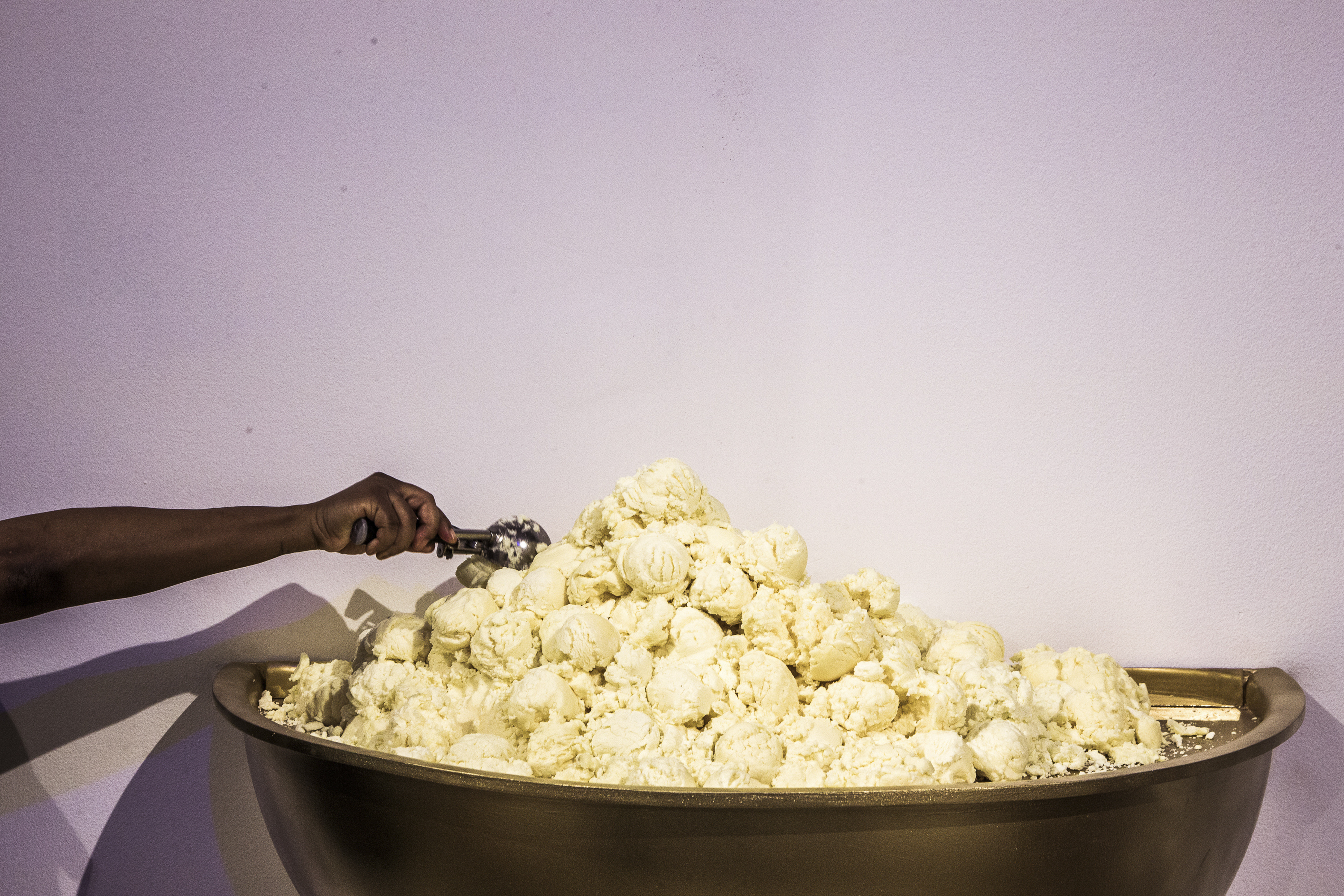 """An attendee scoops vegetable shortening laced with sugar to deposit it into """"The World's Largest Ice Cream Sundae"""" during a press preview of the Museum of Ice Cream in New York."""