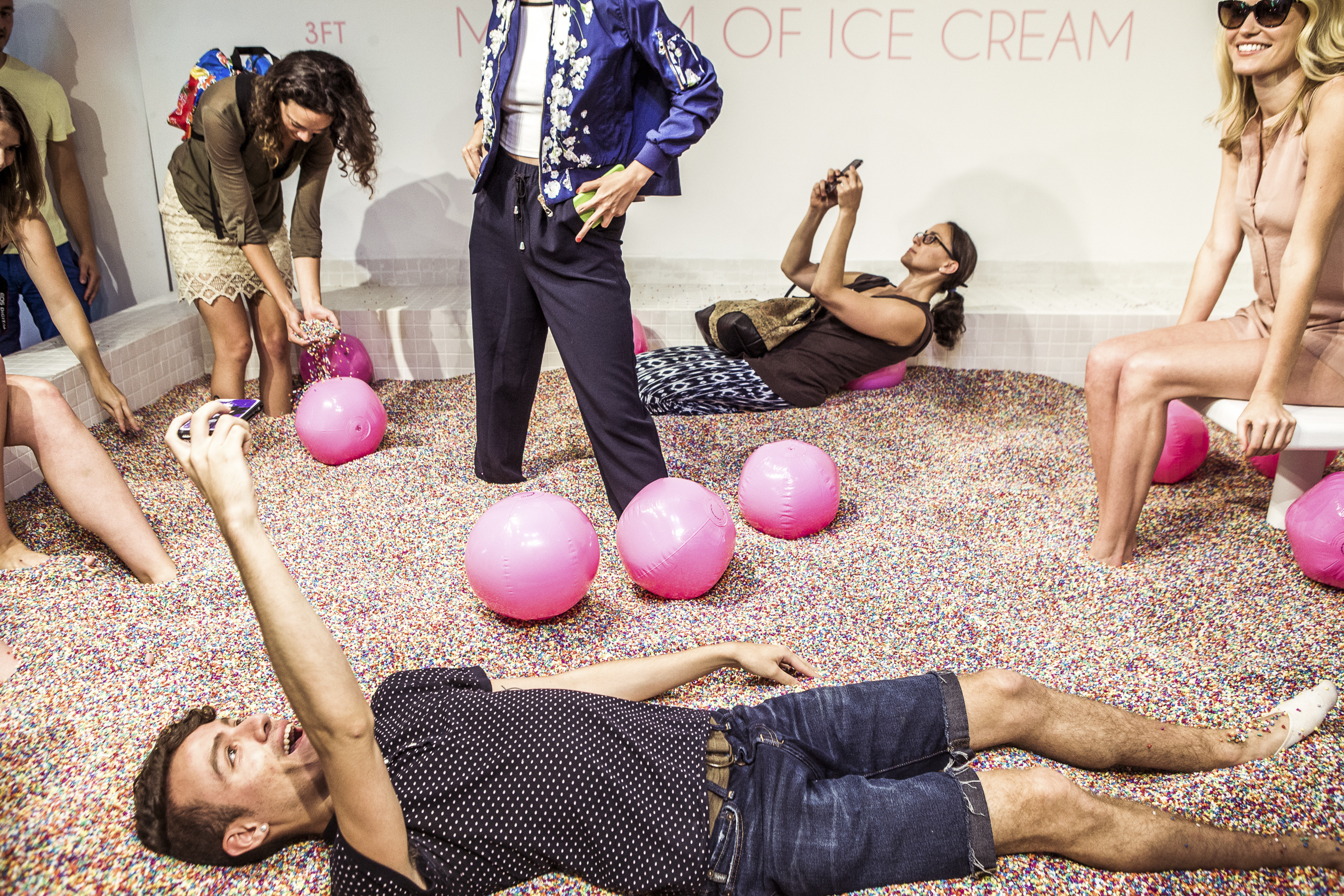 Attendees play and take photos in a pool of non-edible sprinkles during a press preview of the Museum of Ice Cream in New York.