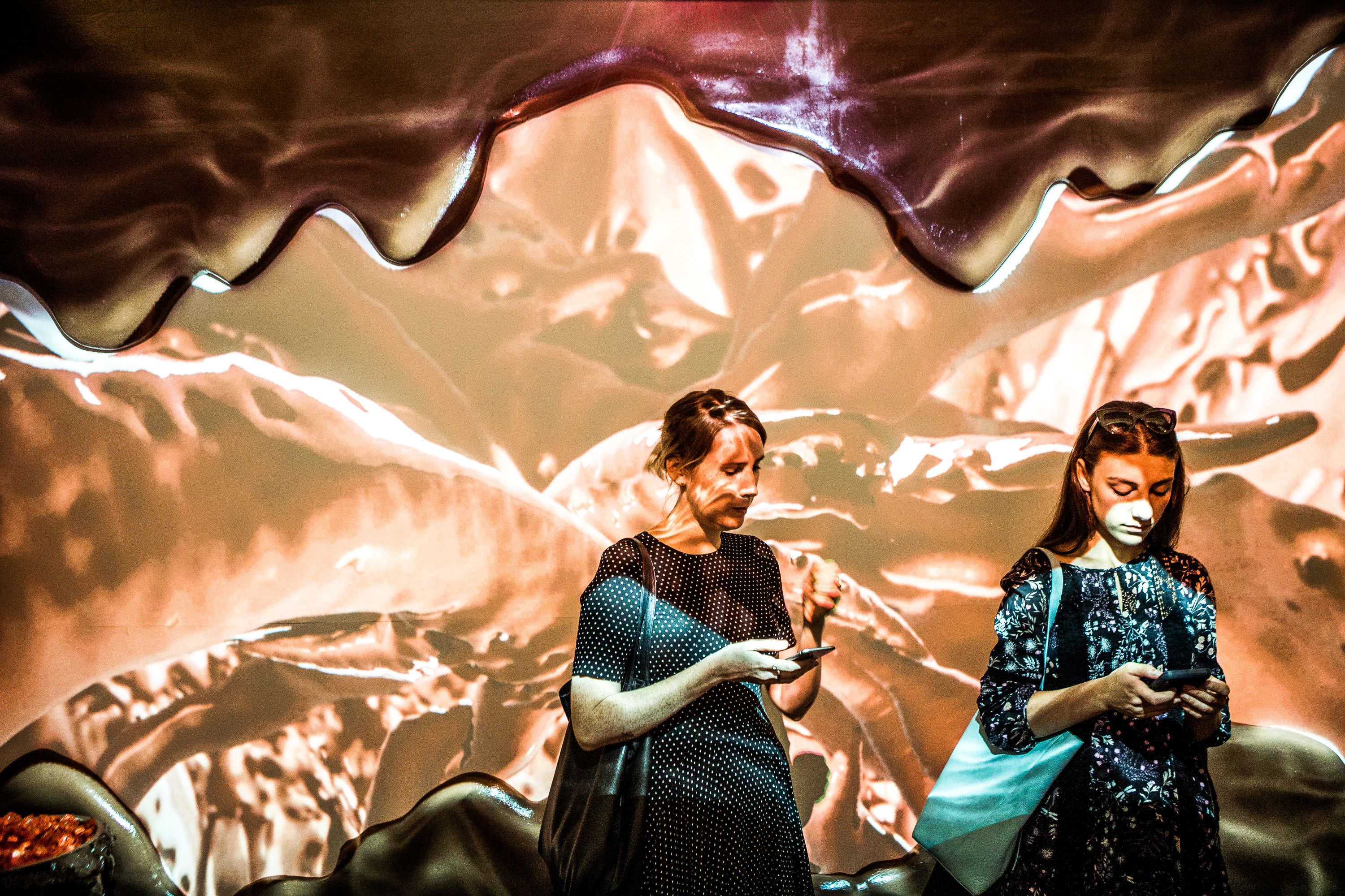 Attendees pass through the chocolate room, where projections of liquid chocolate swirl along the wall, during a press preview of the Museum of Ice Cream in New York.