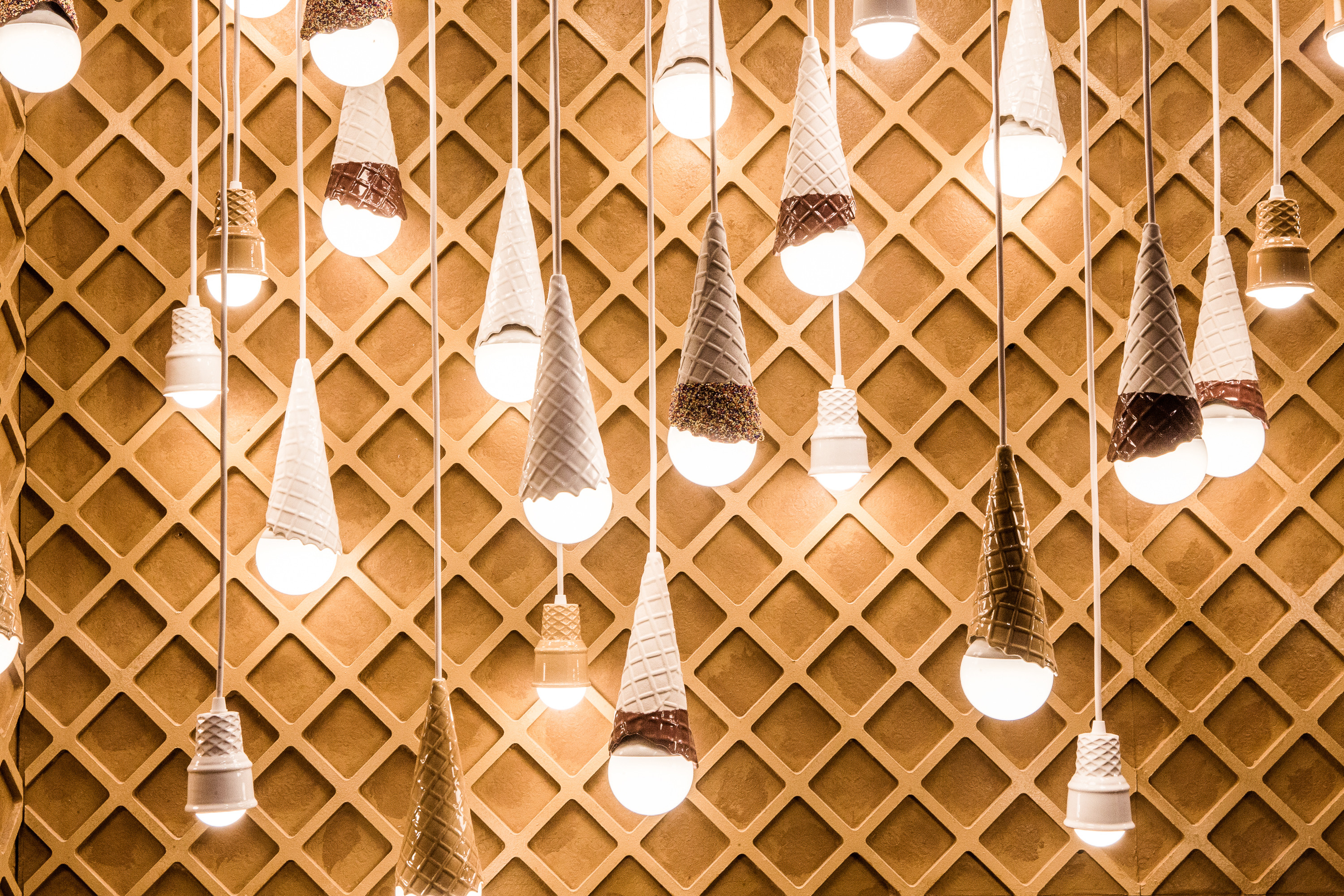 Dangling light fixtures created by artist Alex Garnett in a room dedicated to ice cream cones during a press preview of the Museum of Ice Cream in New York.