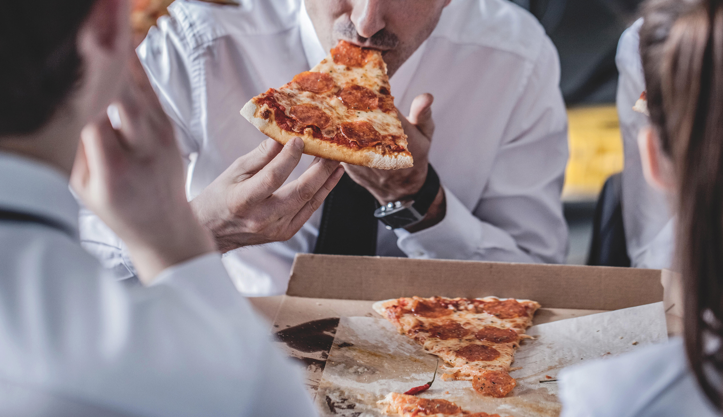 Business team eating pizza in office sitting around the table