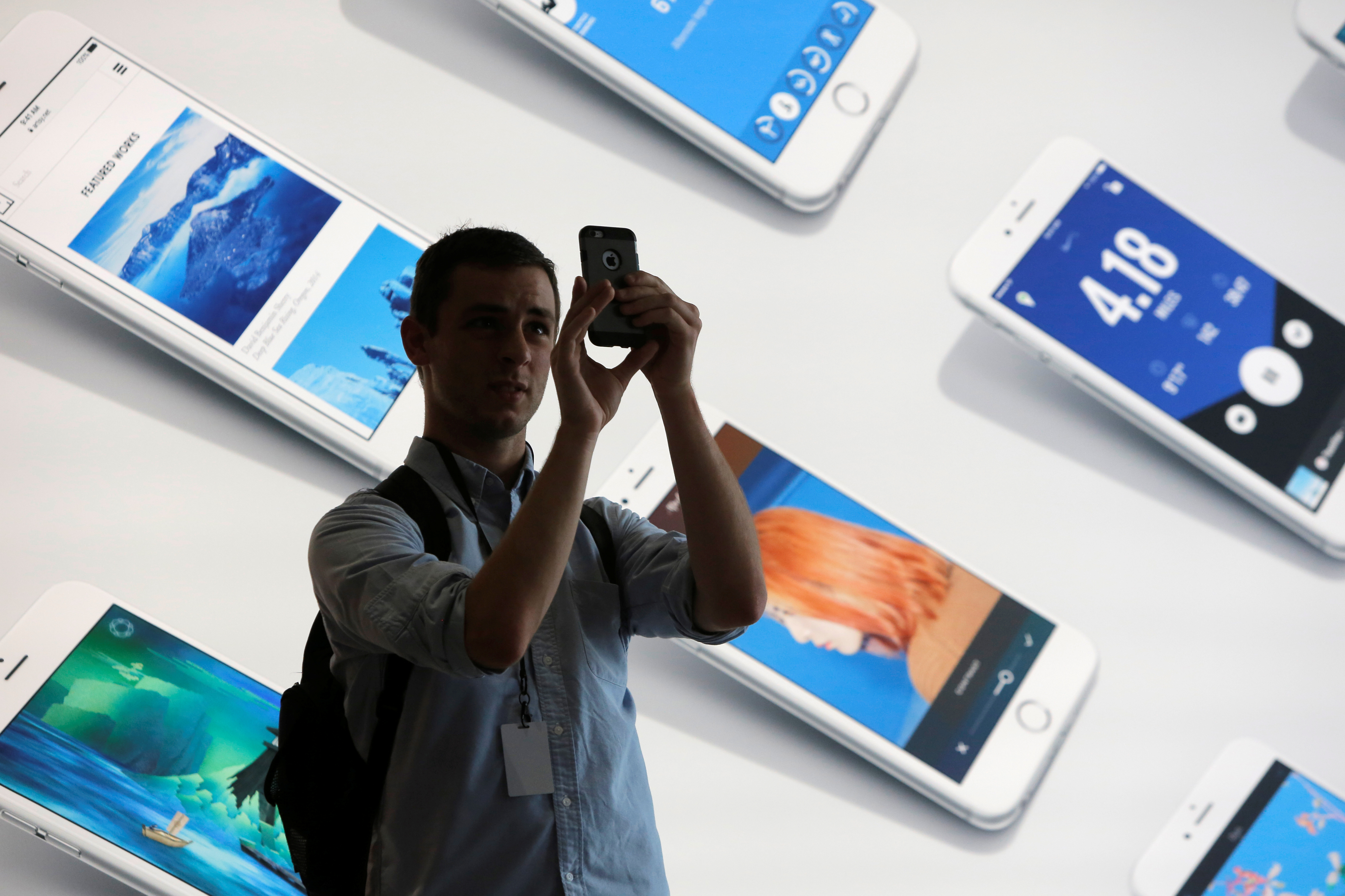 A man uses his iPhone during a preview event at the new Apple Store Williamsburg in Brooklyn, New York