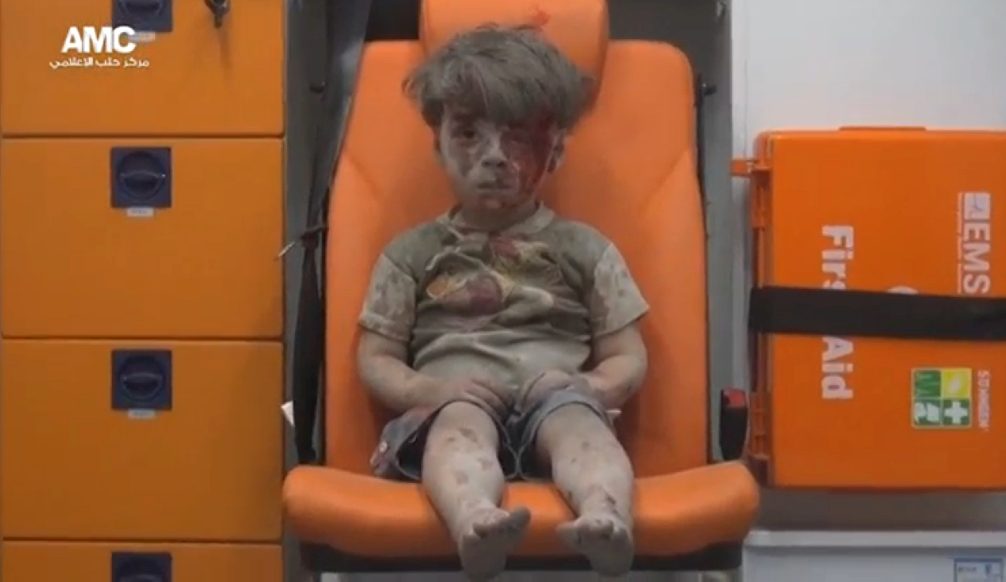 A still image from a video posted on social media shows a boy with bloodied face sitting in an ambulance, after an airstrike