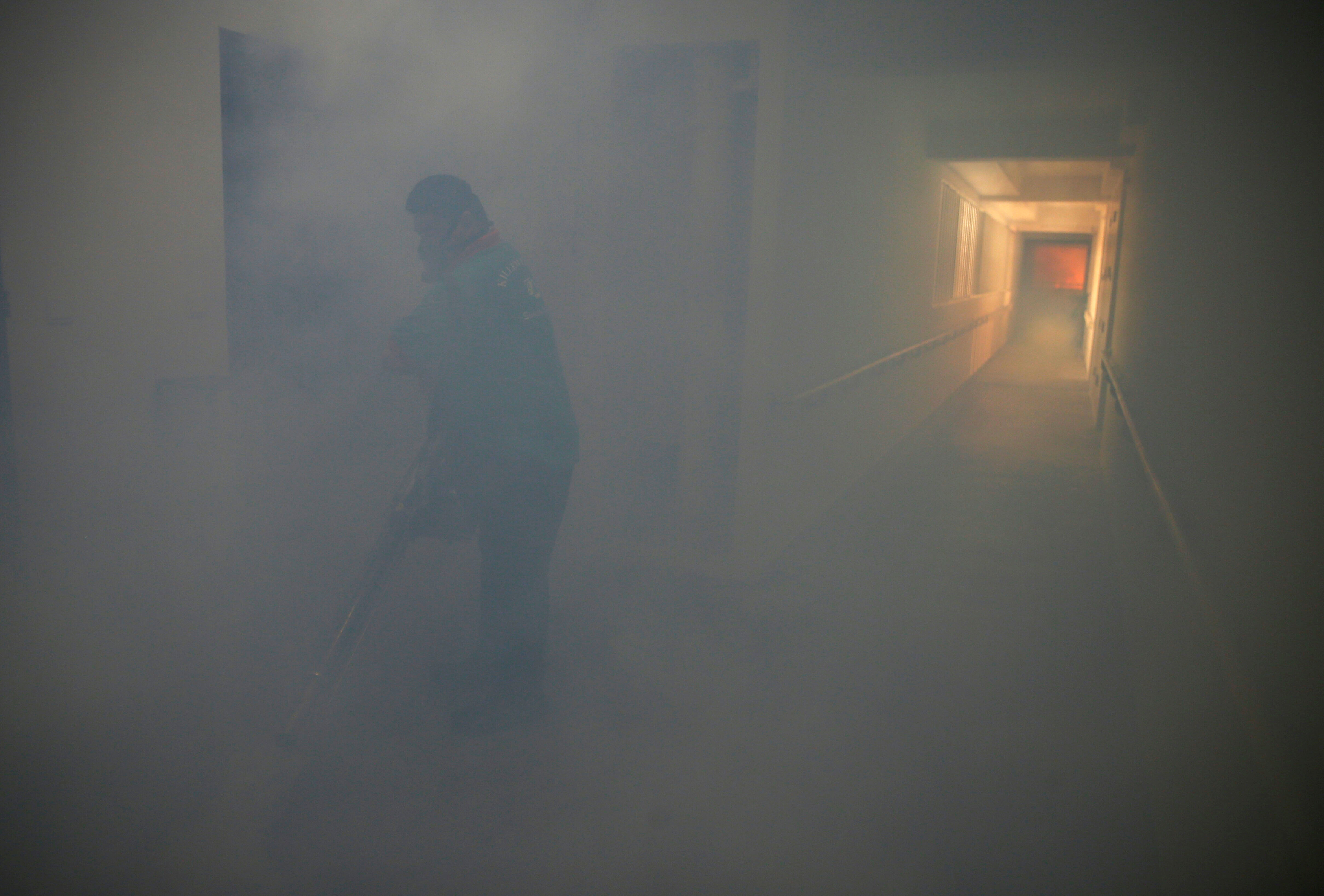 A worker fogs the corridor of a public housing estate in the vicinity where a locally transmitted Zika virus case was discovered, in Singapore