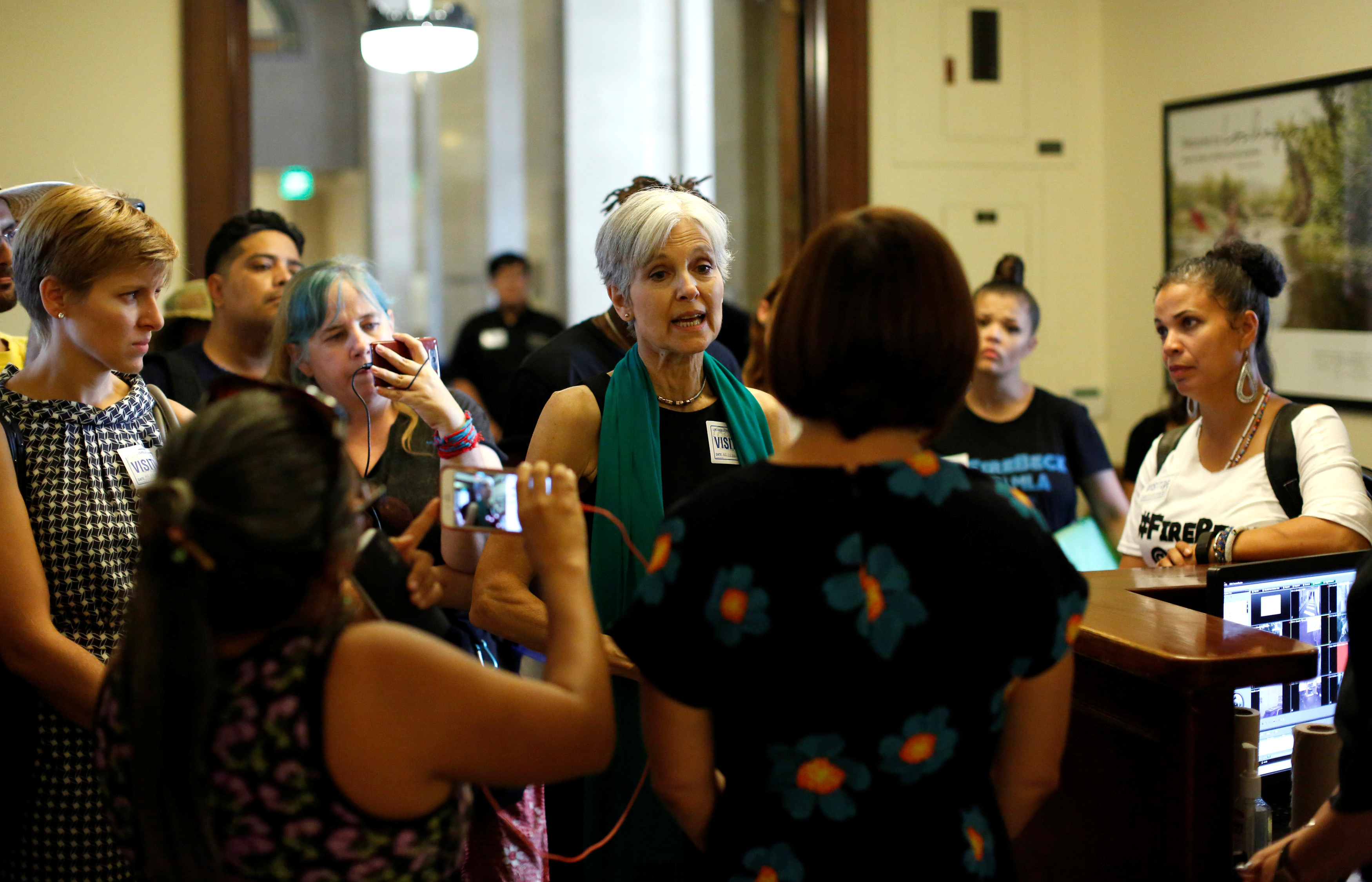 Green Party presidential candidate Stein and activists from Black Lives Matter speak with an employee as they attempt to meet with the mayor at City Hall in Los Angeles