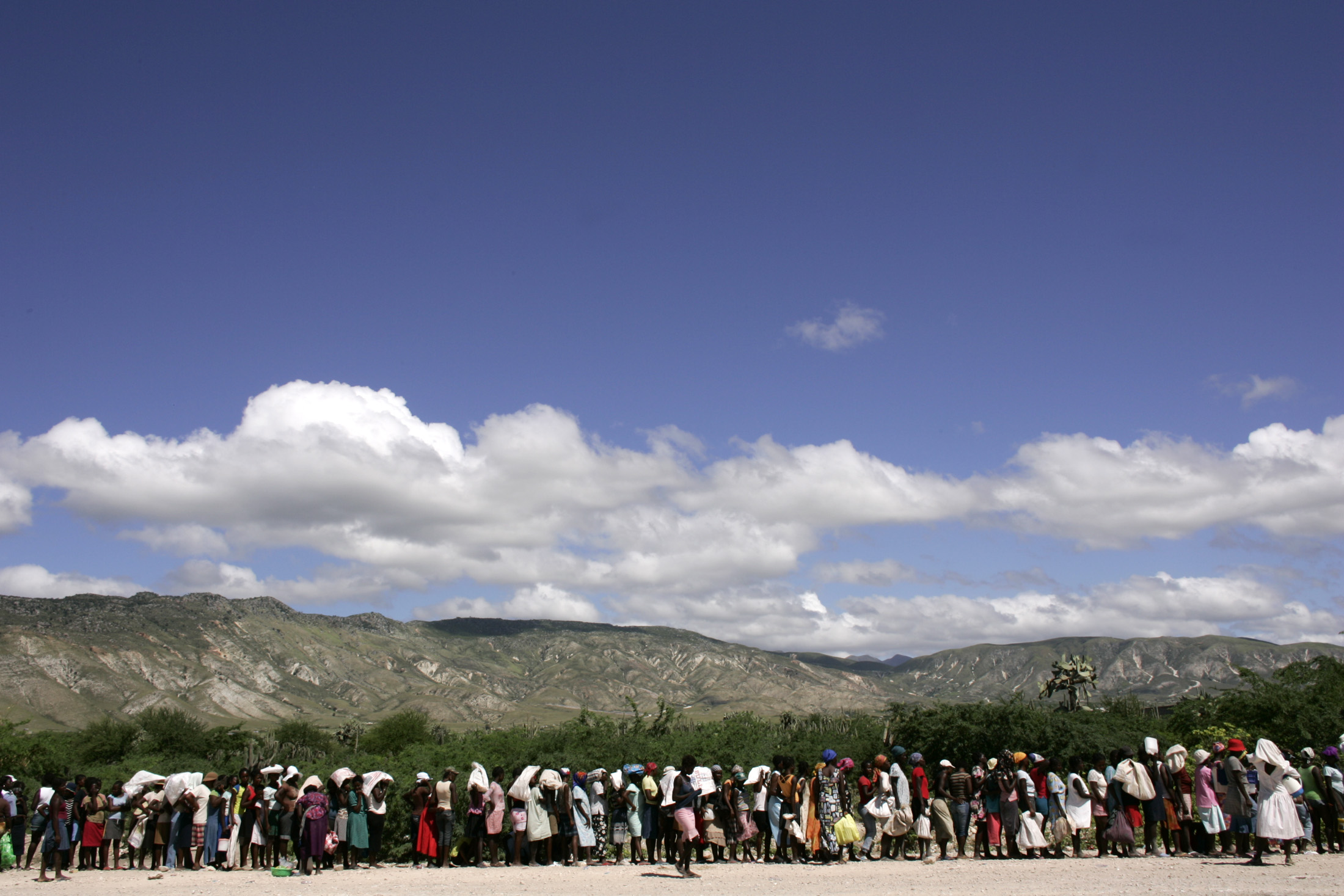 """Haitian women stand in line waiting to get food donated by the NGO CARE and World Food Program """"WFP"""" after flooding in the town of Gonaives"""
