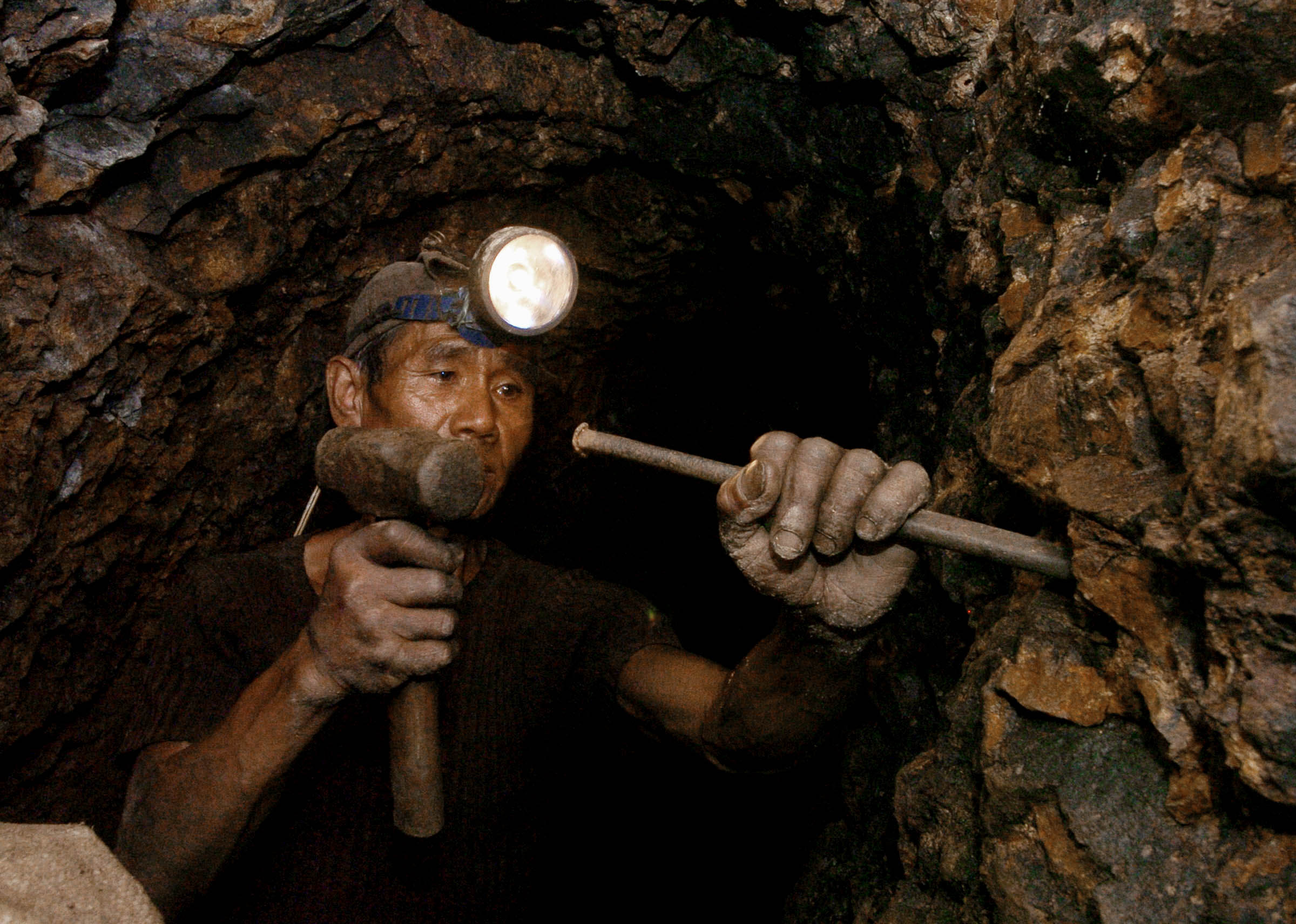 A worker hammers gold ore inside a mine