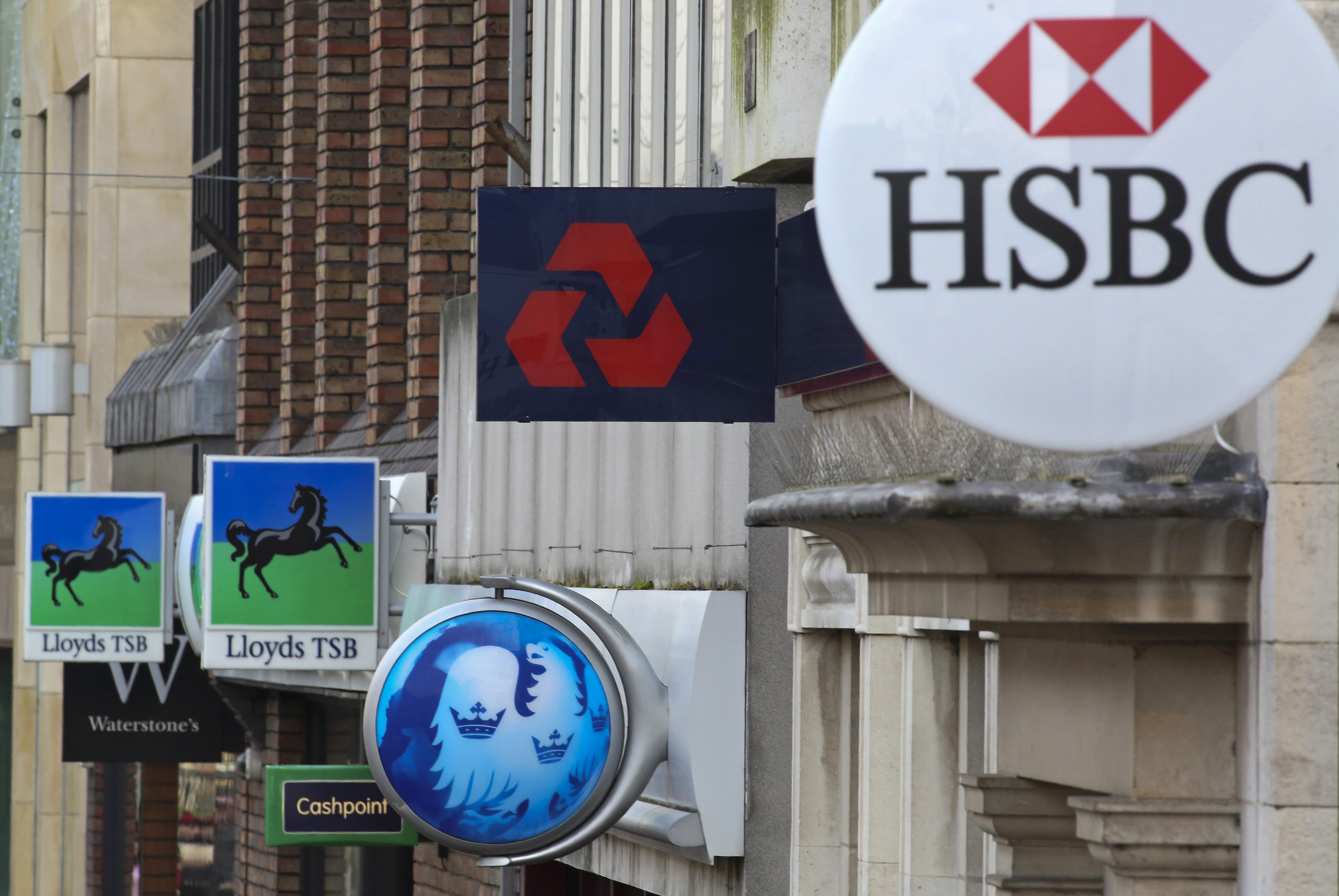 Signs sit outside branches of banks in the UK.