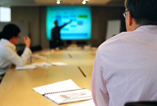 A scene in a meeting where a businessman presents with digital projection on a screen.