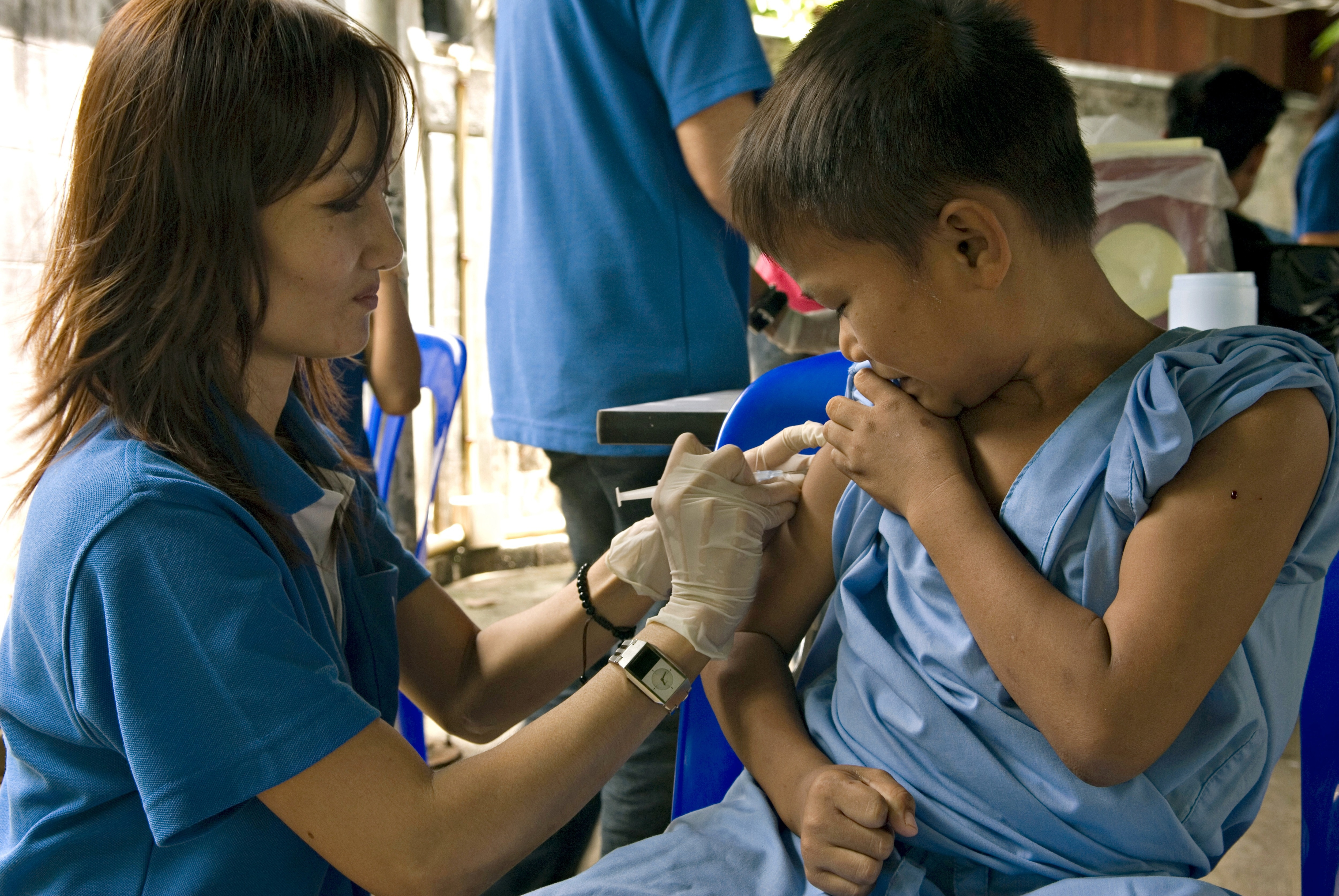 A nurse is vaccinating a young Burmese refugee candidate to
