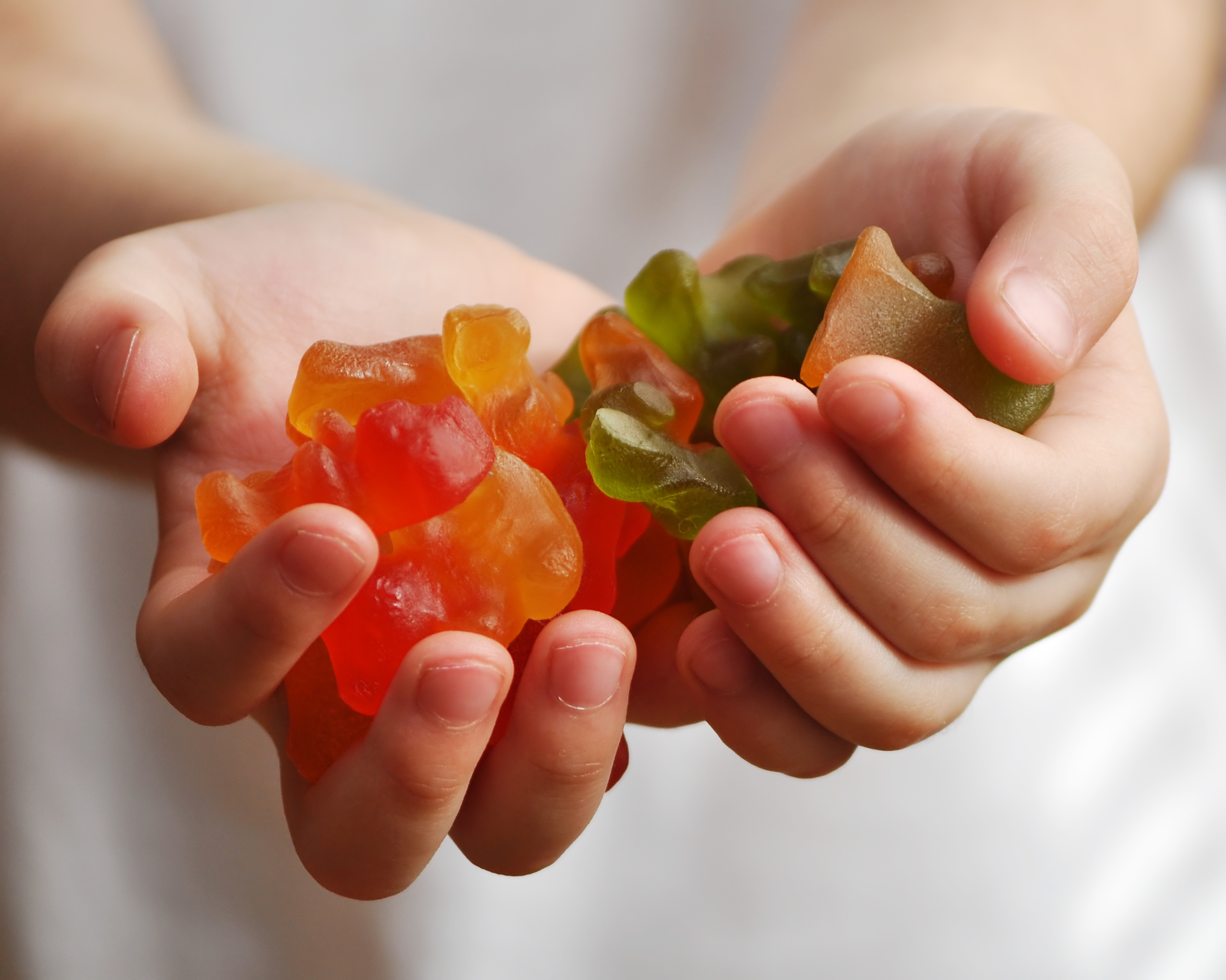 Gummy candies in child hands: Children's hands hold a lot of