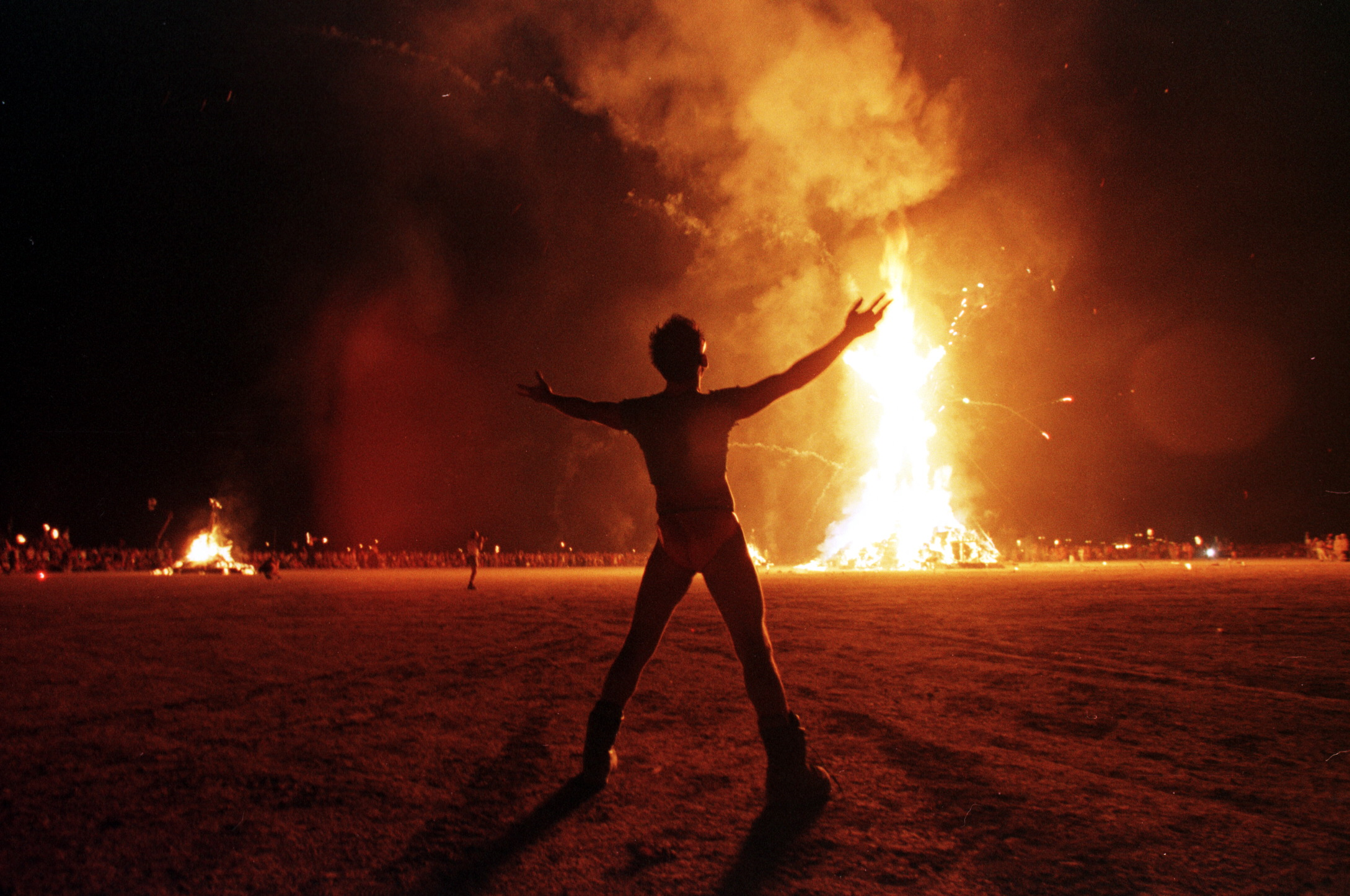 "A ""Burning Man"" participant holds up his arms as t"