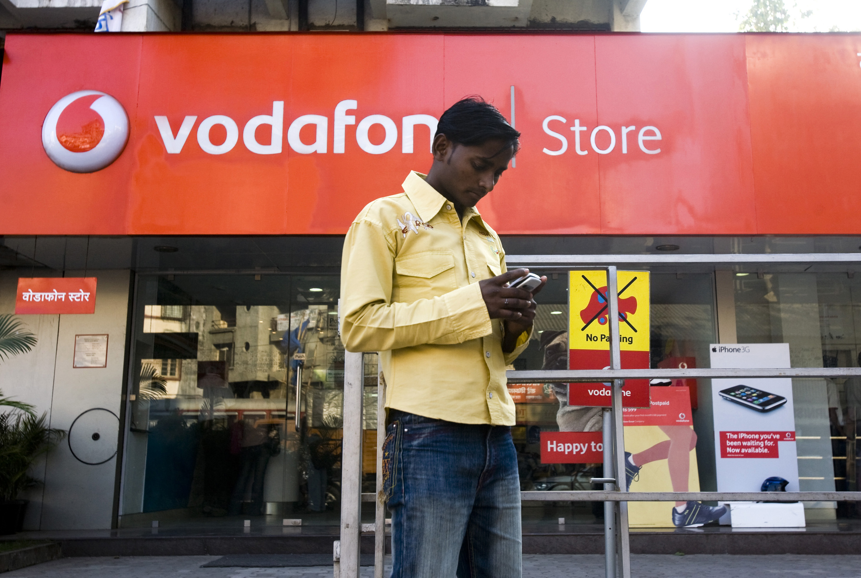 A pedestrian using a mobile phone stops outside a Vodafone s