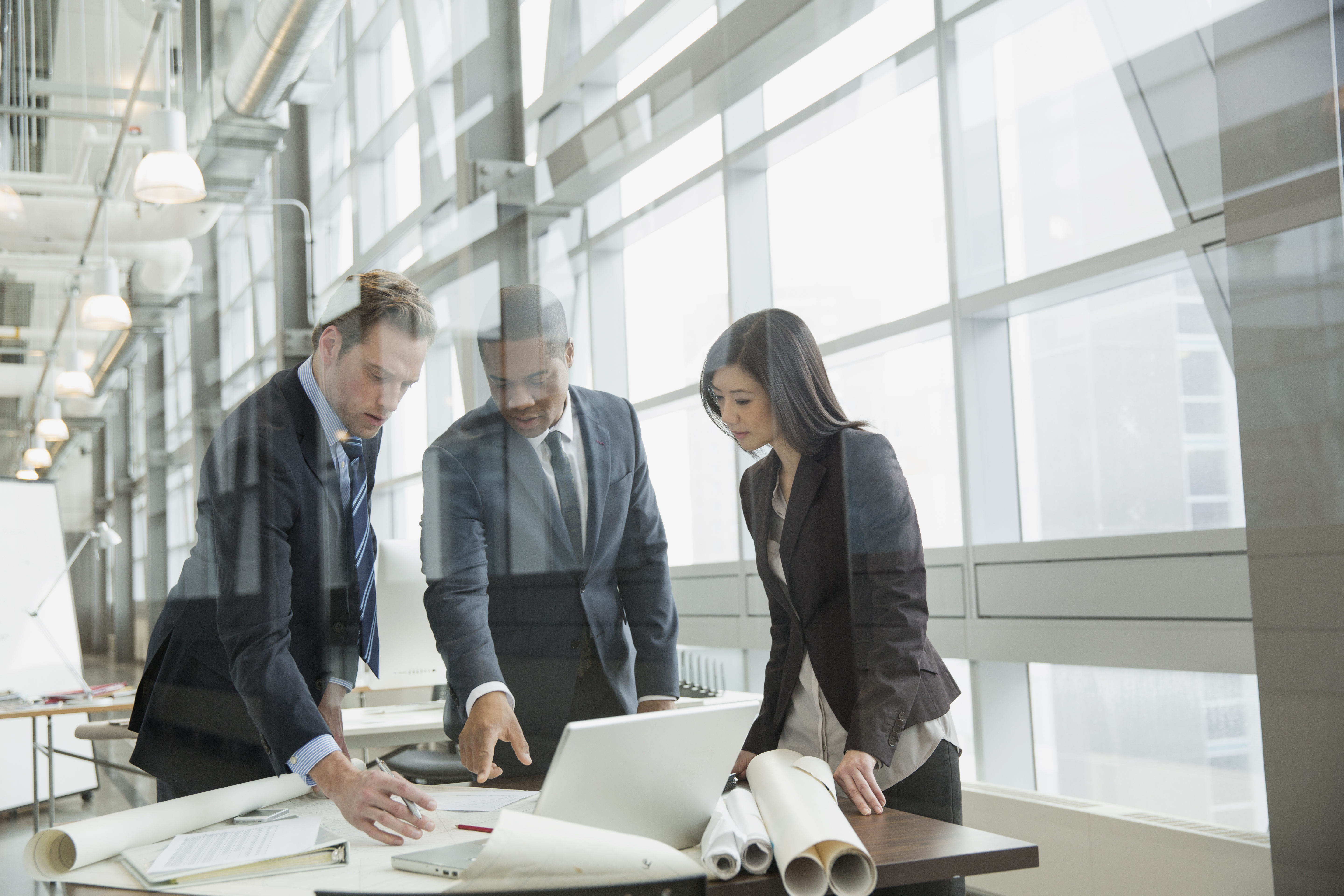 Business people reviewing blueprints at desk
