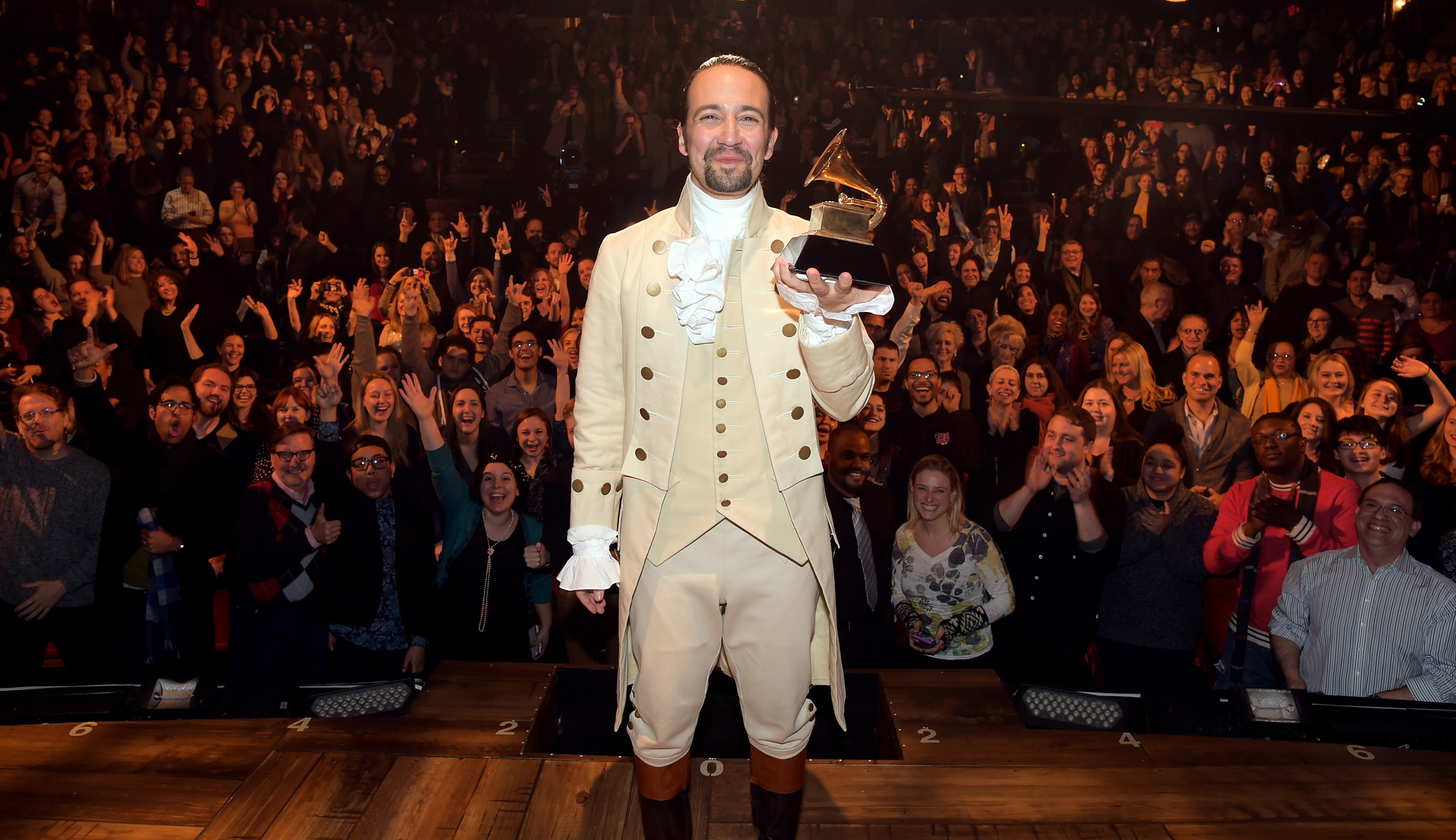 """Lin-Manuel Miranda celebrates receiving the GRAMMY award for """"Hamilton's"""" Best Musical Theater Album on stage during a February 2016 performance."""