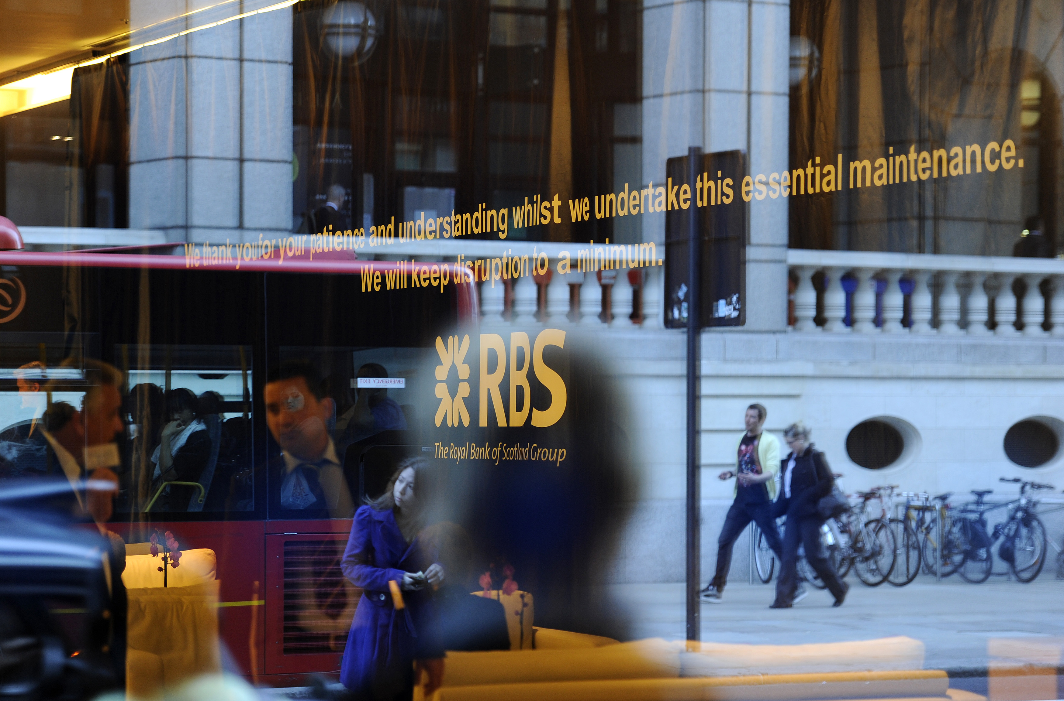 Pedestrians are reflected in the window of a Royal Bank of Scotland building in the City of London