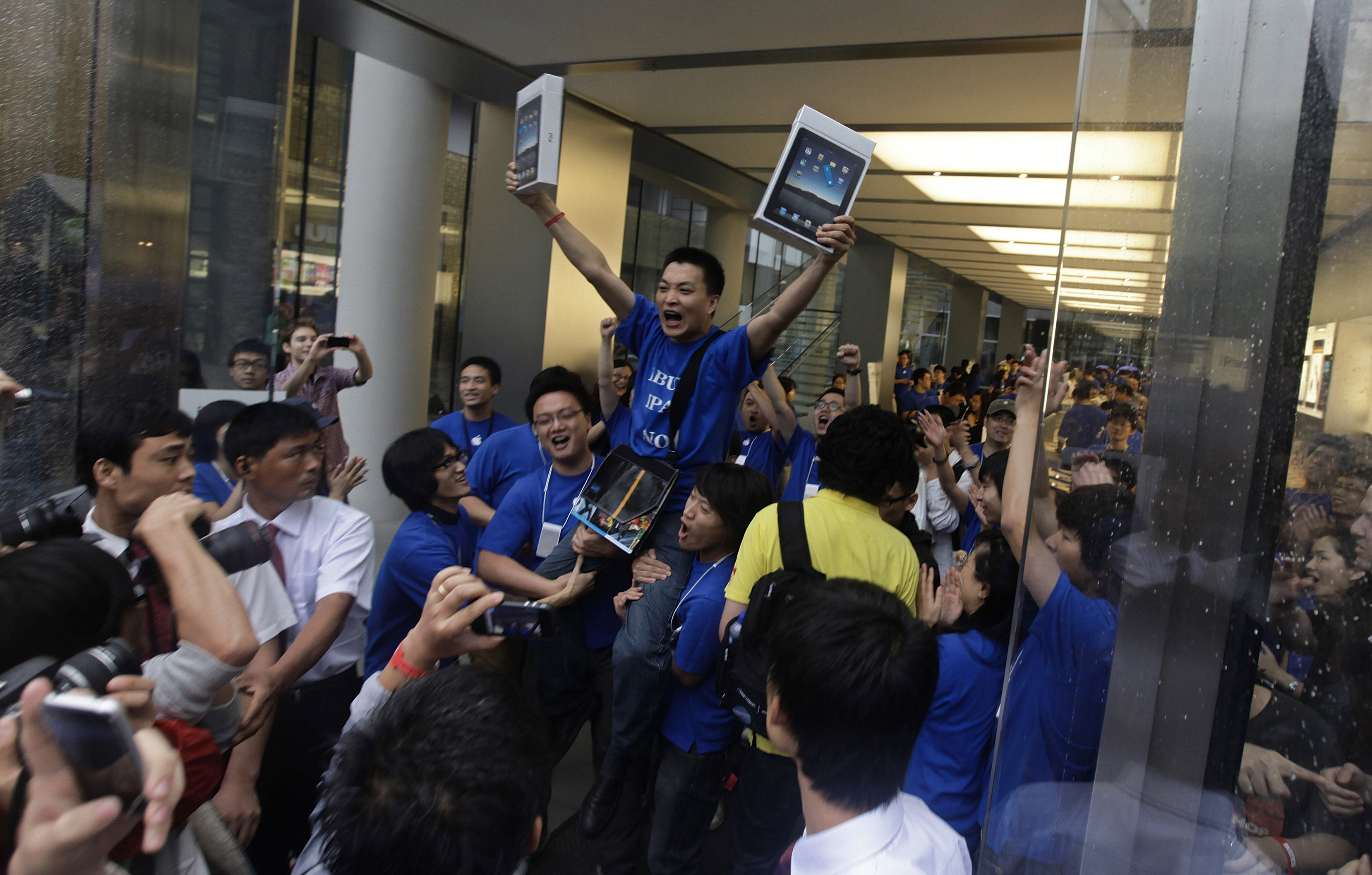 Customer Han Ziwen holds up his iPads at an Apple flagship store in Beijing