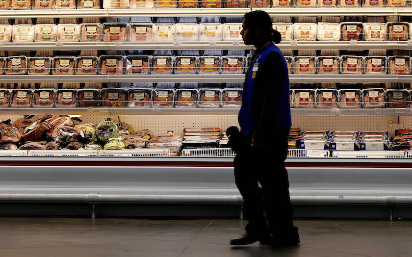 A employee walks by a meat cooler in the grocery section of a Sam's Club during a media tour in Bentonville