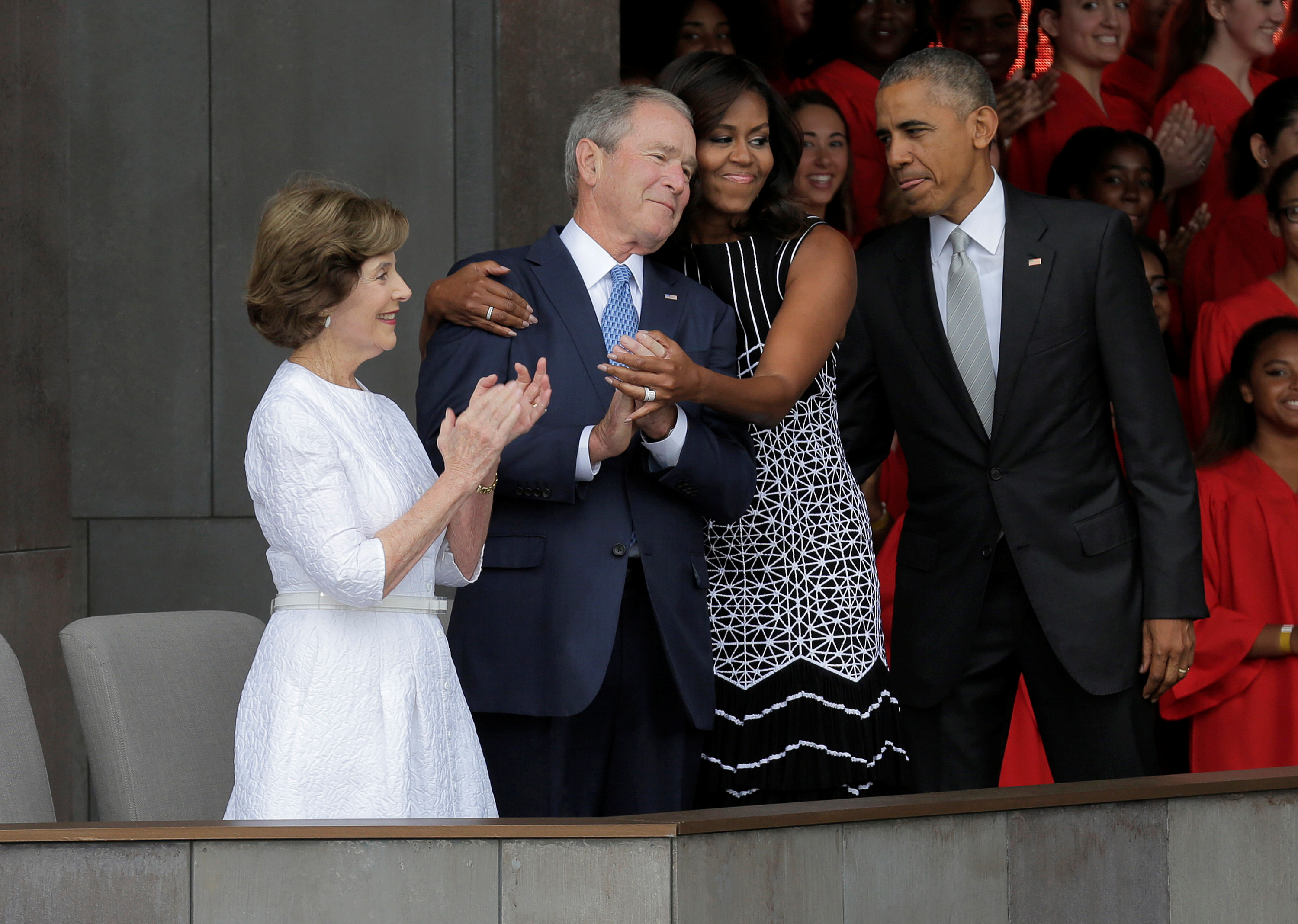 U.S. First Lady Michelle Obama hugs former U.S. President George W. Bush as she arrives for the dedication of the Smithsonian's National Museum of African American History and Culture in Washington