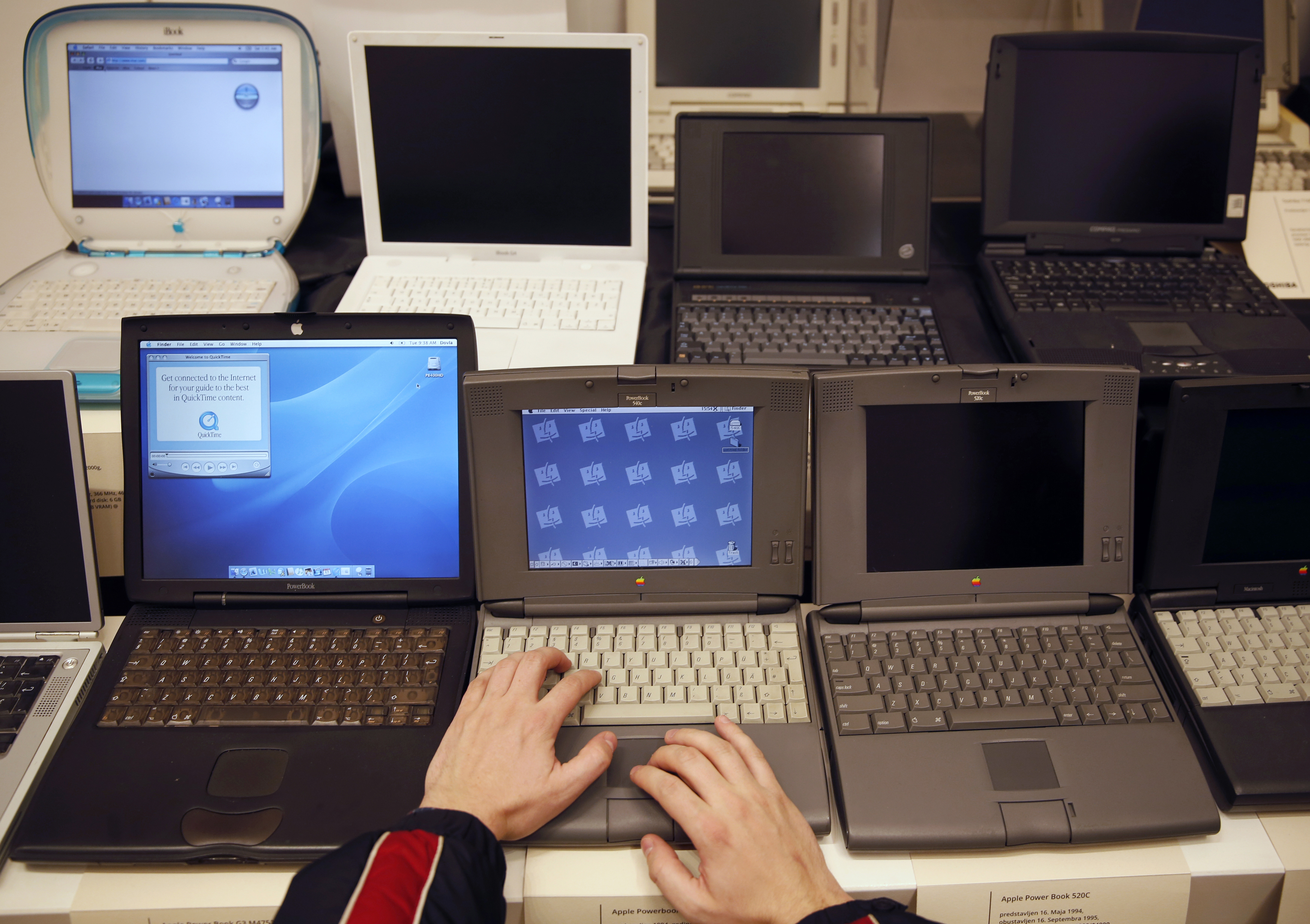 "A man works on an Apple PowerBook 540c laptop during the ""History of Computers"" exhibition in Sarajevo"