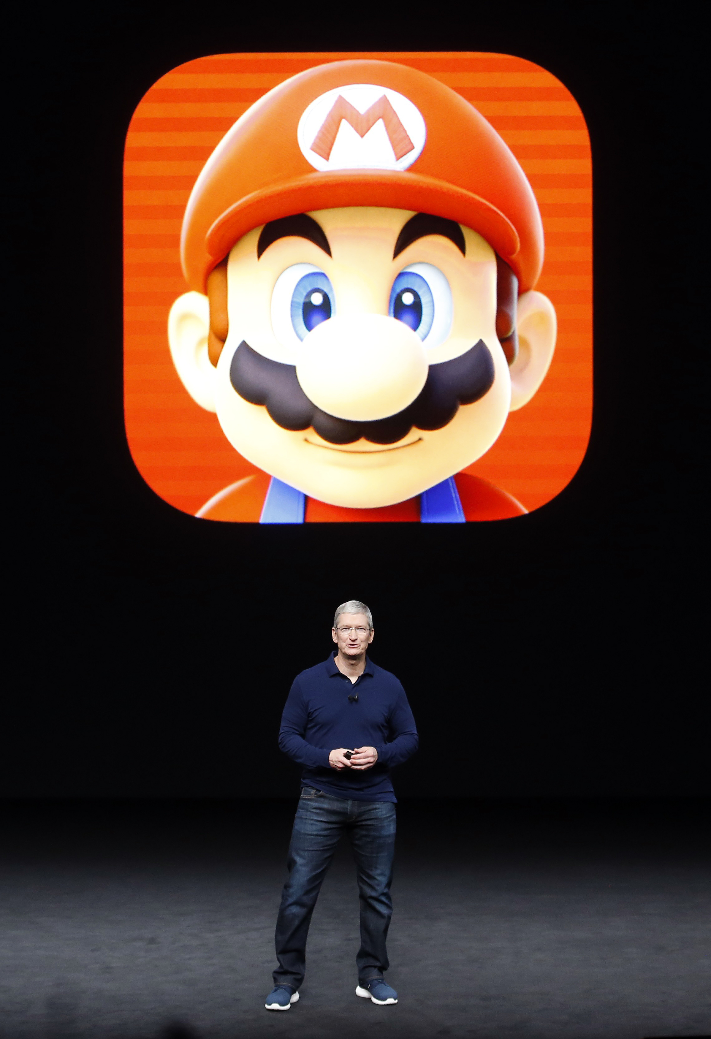 Tim Cook speaks in front of a Mario Bros. image during an Apple media event in San Francisco